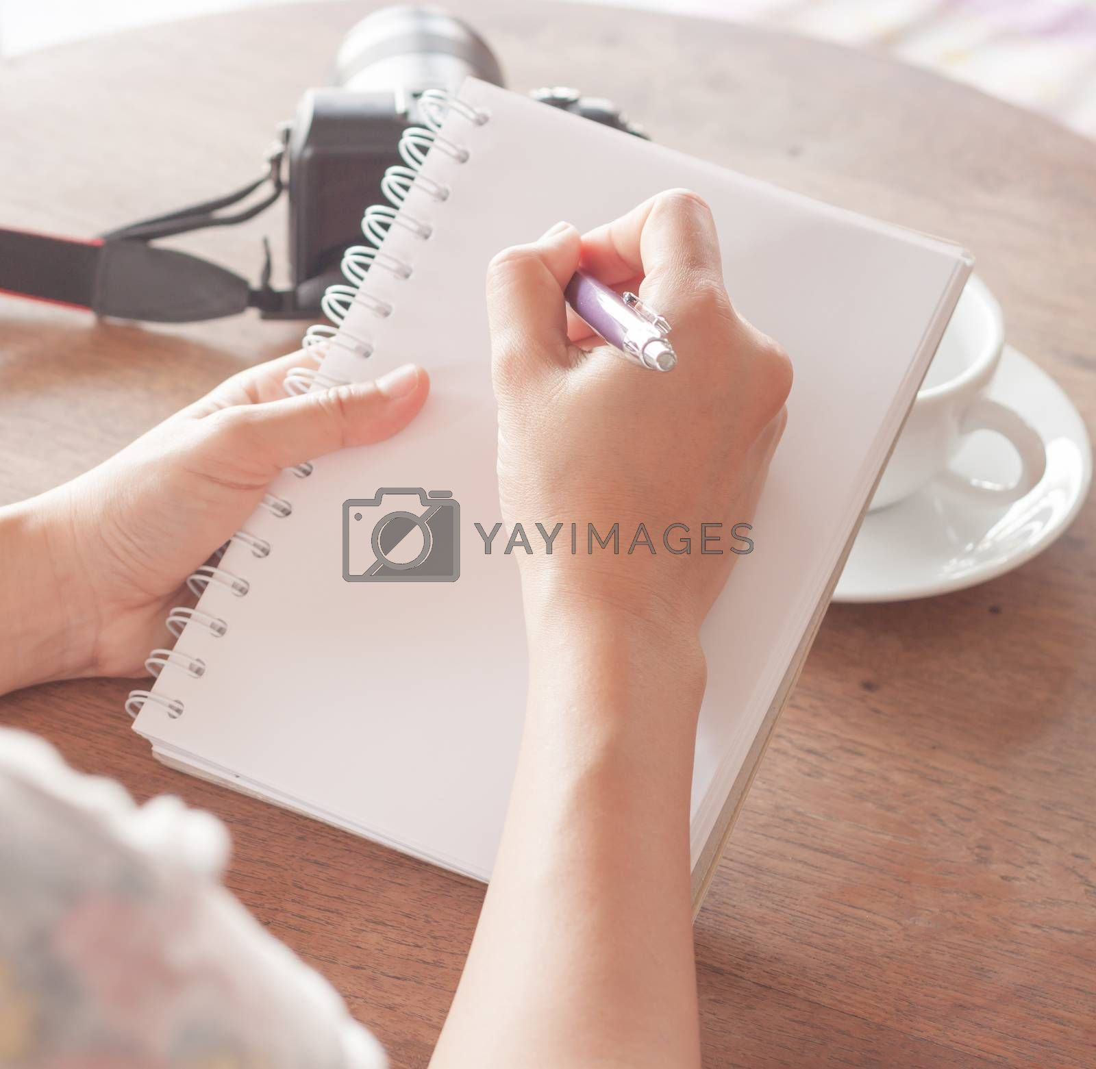 Woman hand with pen writing on notebook, stock photo
