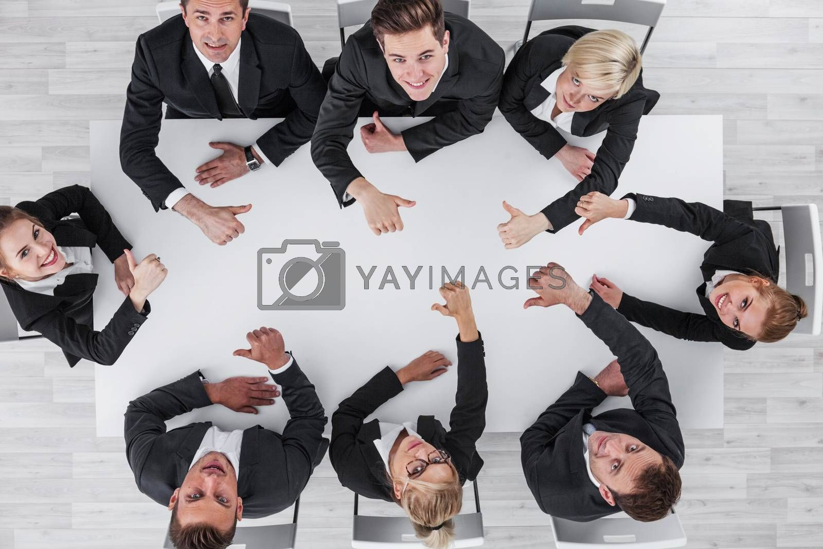 Diverse business people sitting around the table on a meeting and smiling