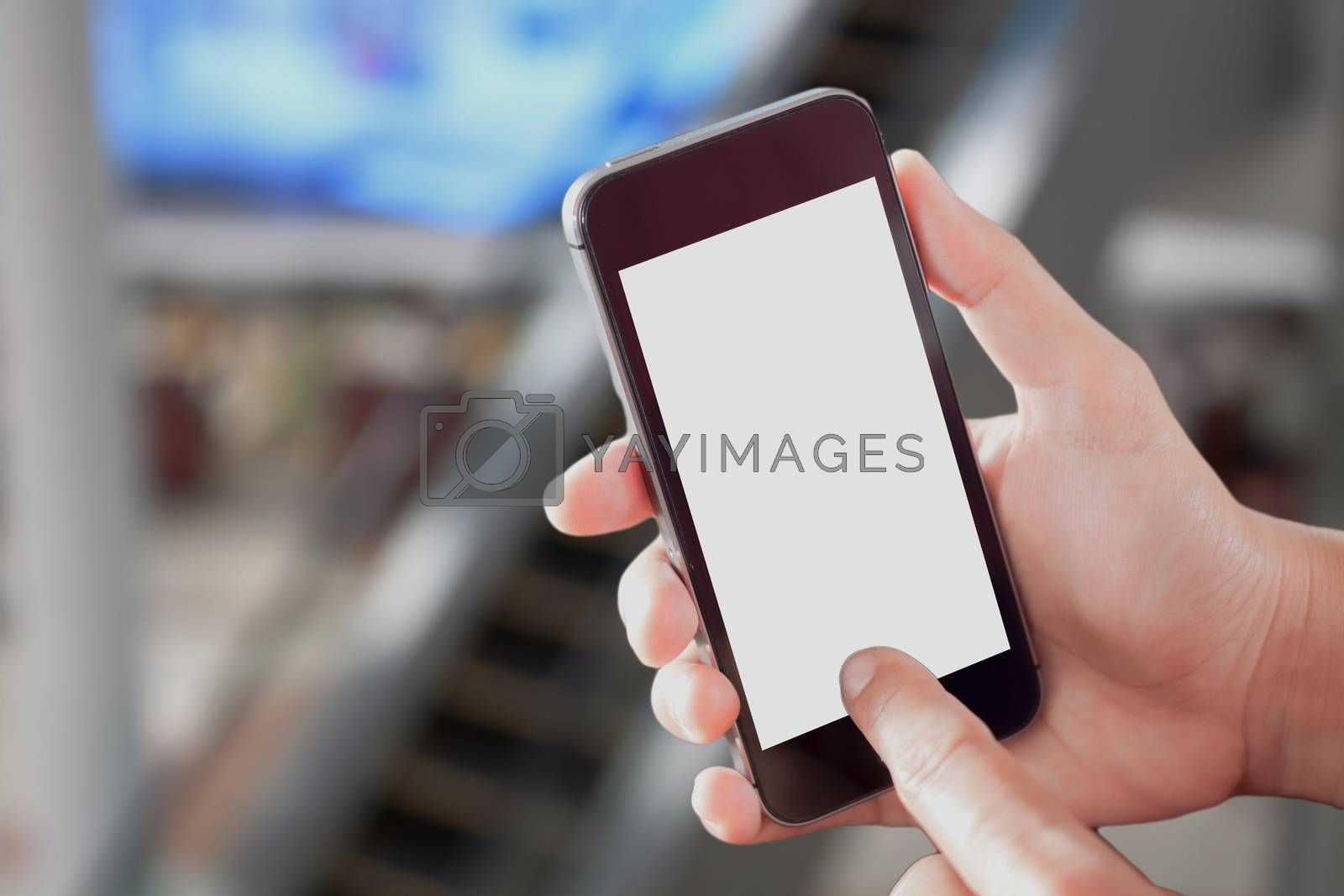 Hand holding smart phone with white screen on blurred background, stock photo