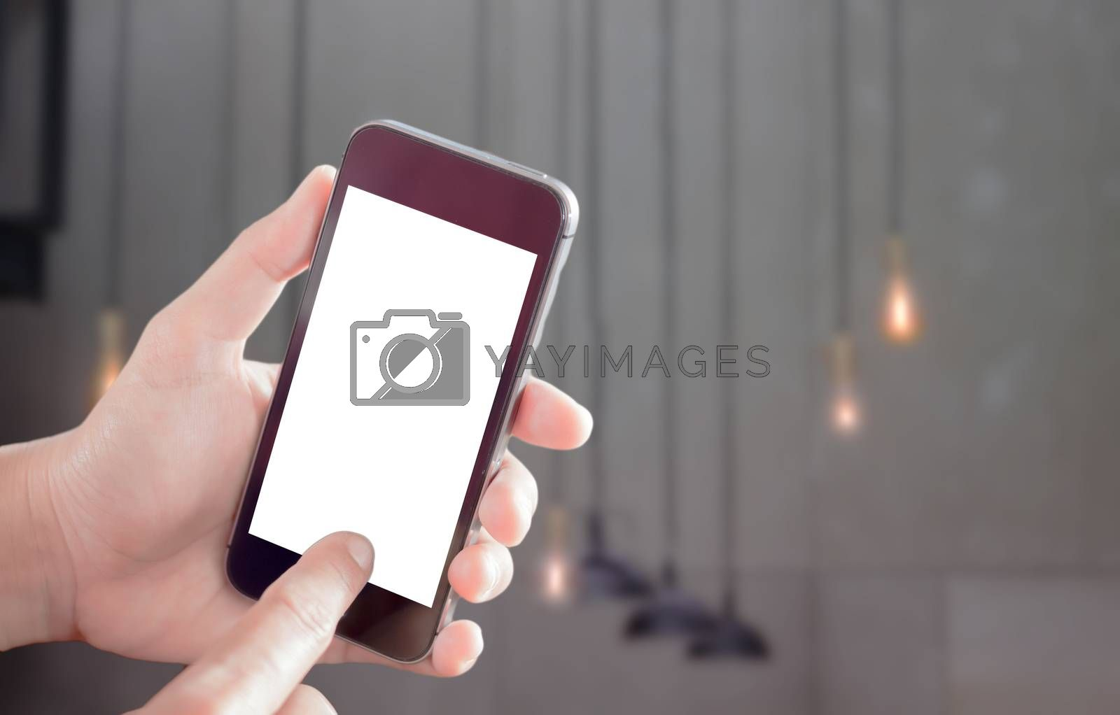Hand holding smart phone with light blurred background, stock photo