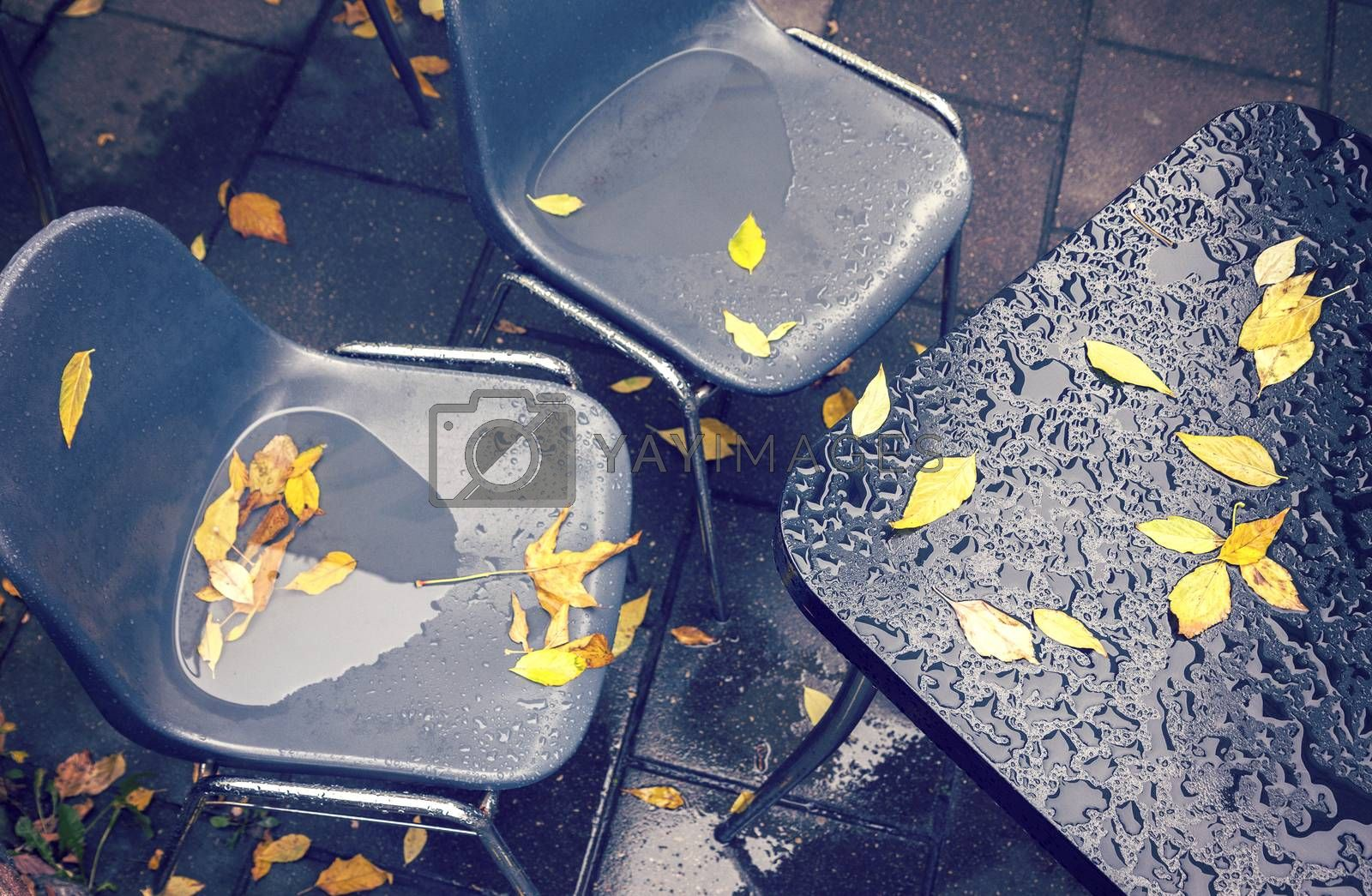 Messy and rainy plastic cafe chairs and table at autumn