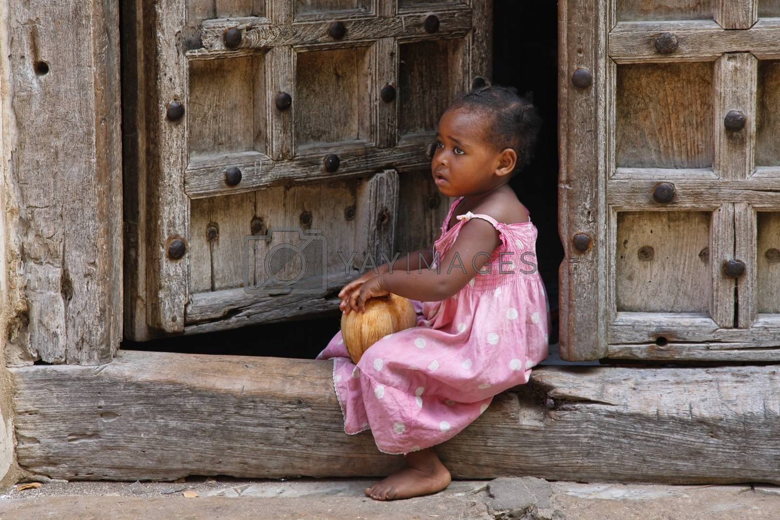 Stone Town, Tanzania - December 30, 2015: Traditional house with old door and small girl sitting on the street of Stone Town.