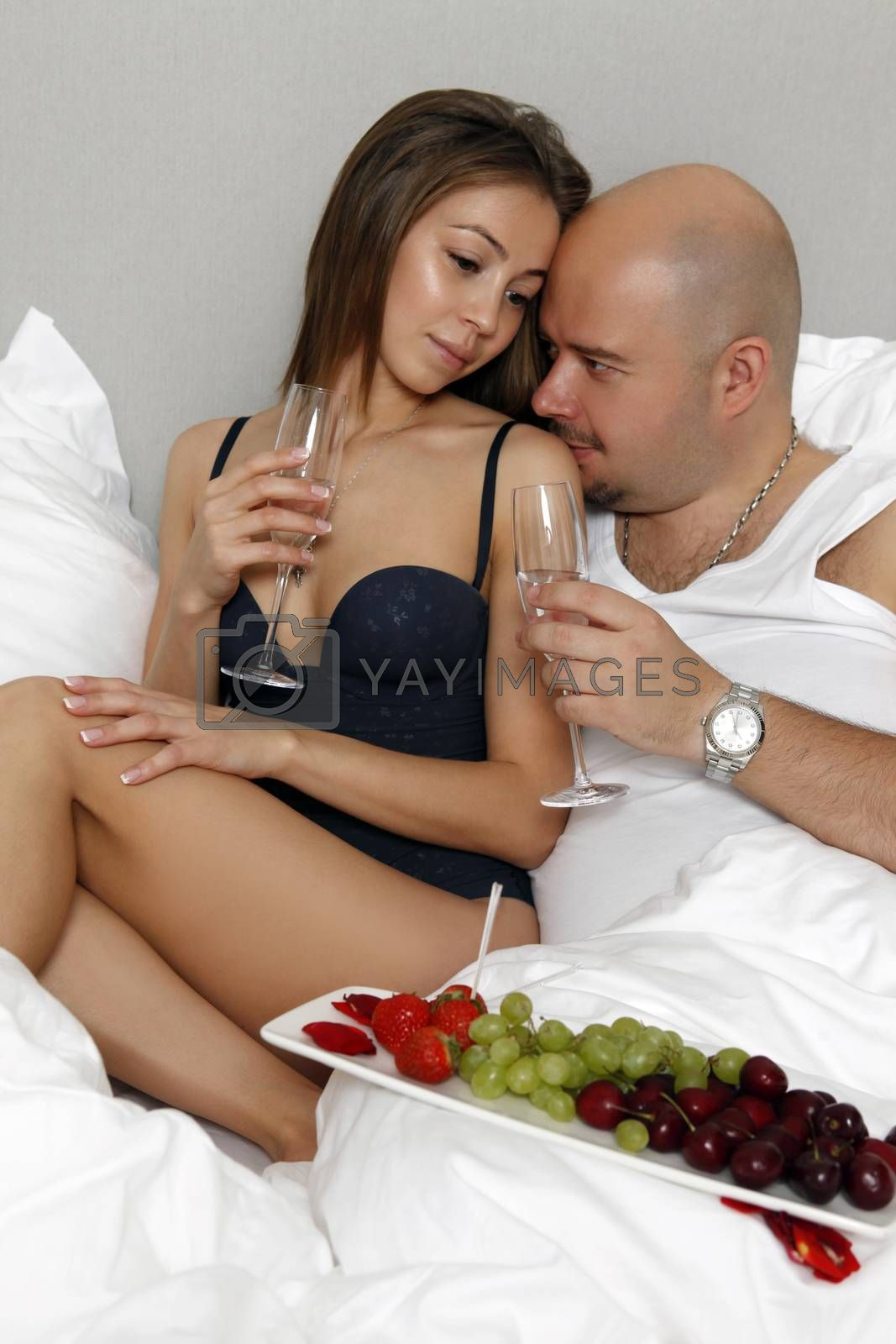 Loving couple in bed drinking champagne