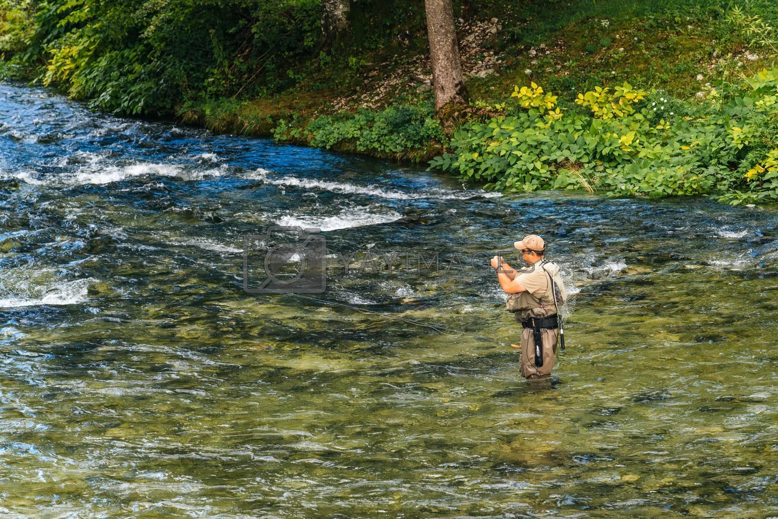 Unidentifiable man fishing at Jezernica river, Bohinj Lake by stevanovicigor