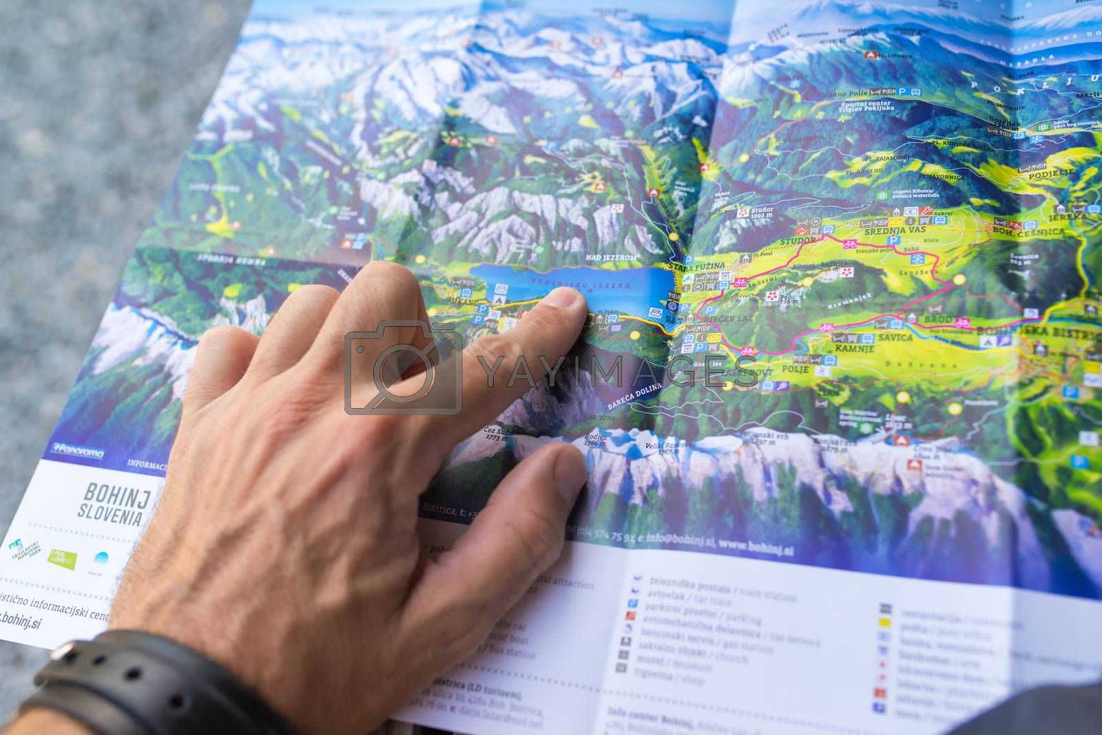 Unidentifiable man looking at map of Bohinj lake area by stevanovicigor