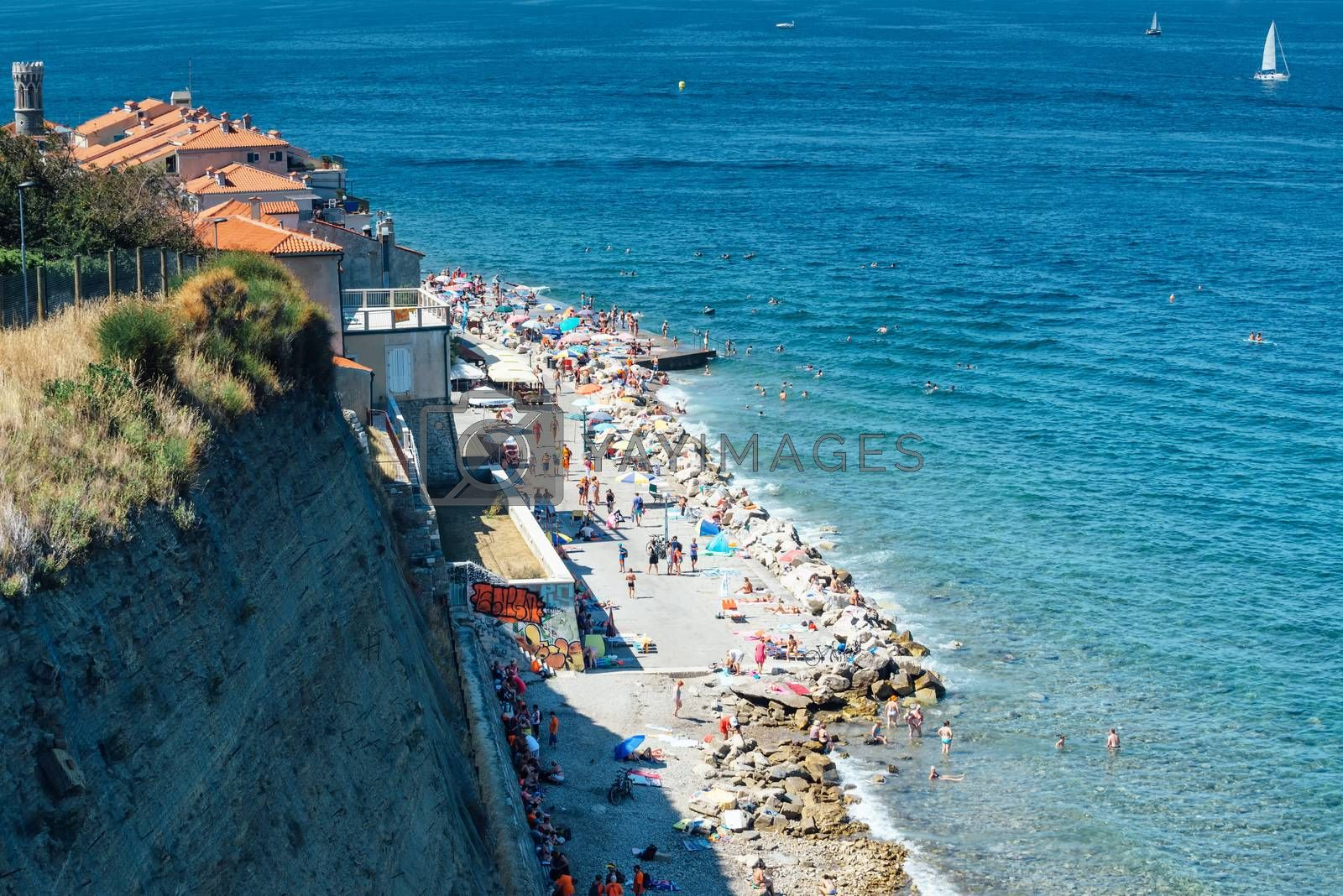 PIRAN, SLOVENIA - AUGUST 27. 2016: Unidentified people on beach in the pictoresque village of Piran on Slovenian Adriatic sea