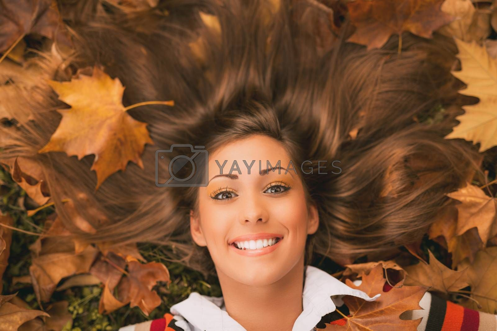 Portrait of a beautiful young woman in forest in autumn colors. She is lying on the fall leaf and enjoying. Looking at camera. Close-up.
