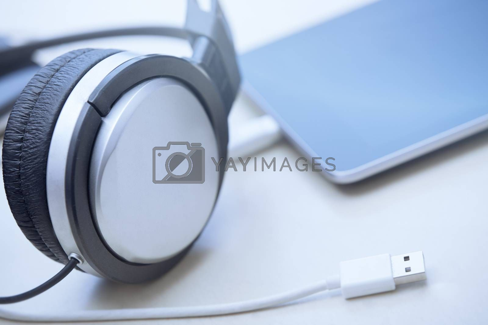 Headphones digital tablet and USB cable laying on a table