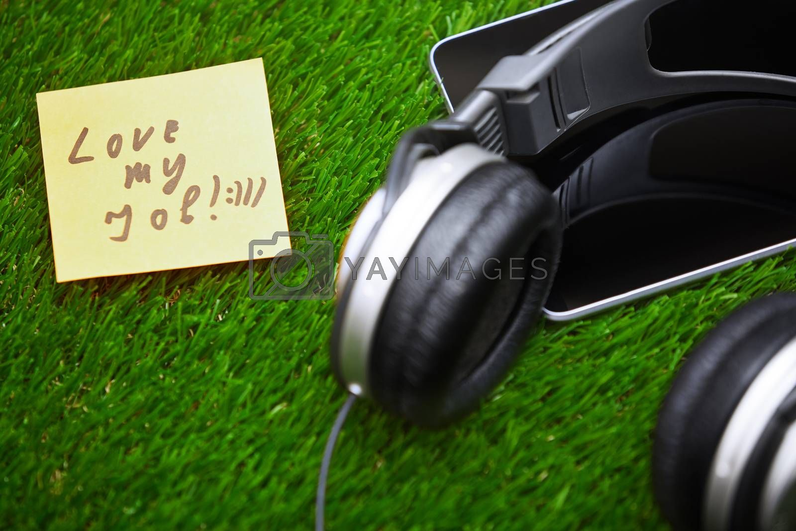Text on sticky note on a grass with headphones and digital tablet
