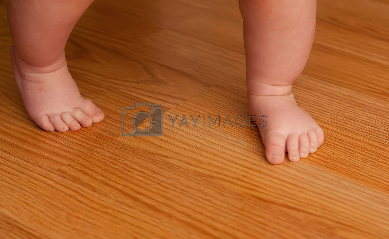 Young girl walking on a hard wood floor for her first time