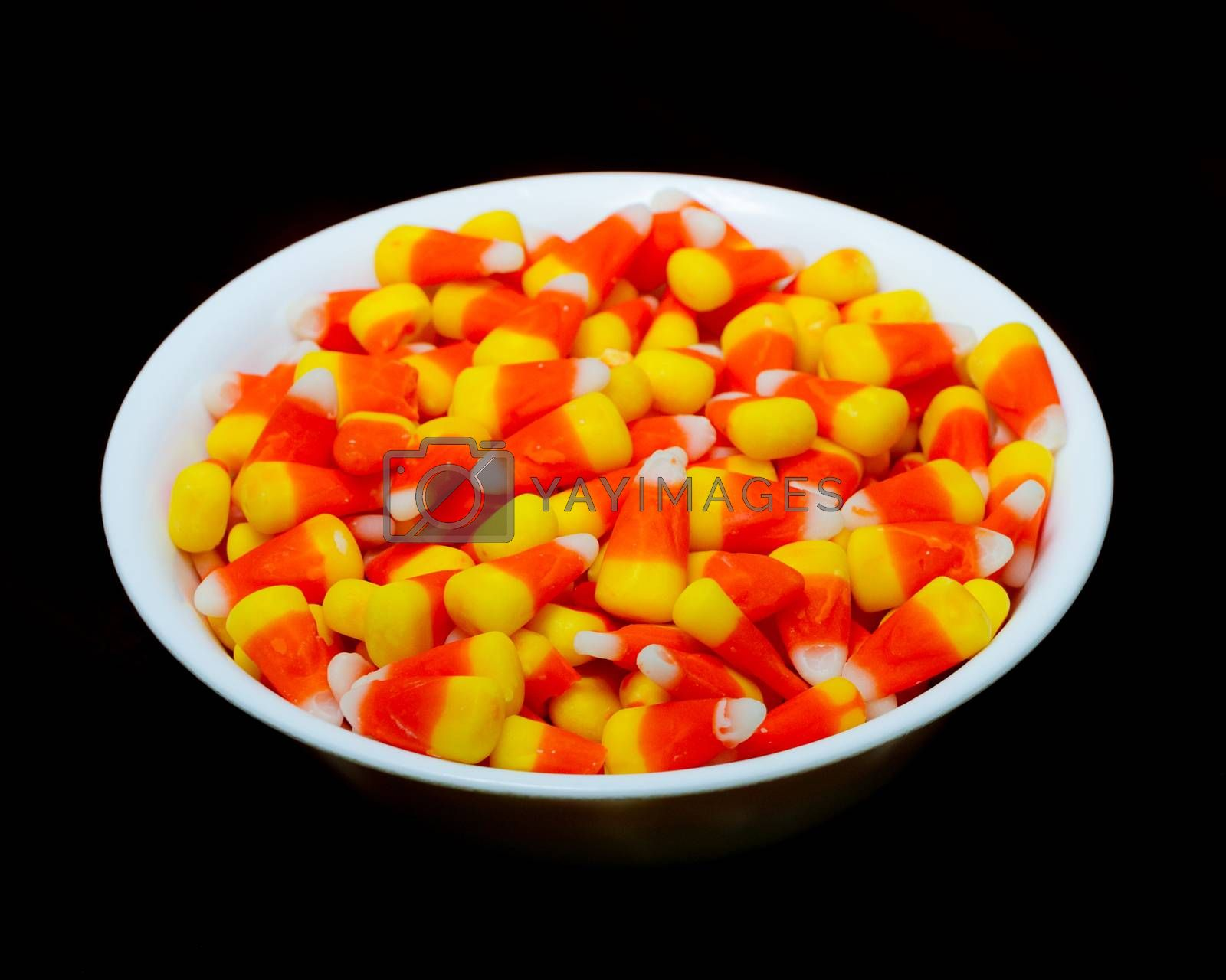 Candy Corn in a bowl isolated against a black background