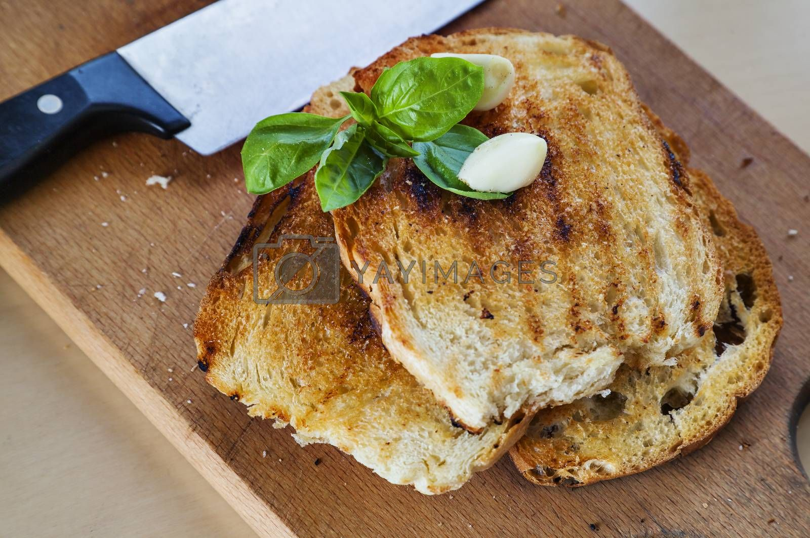 Three roasted slices of bread with garlic, fresh basil and a knife on the side.