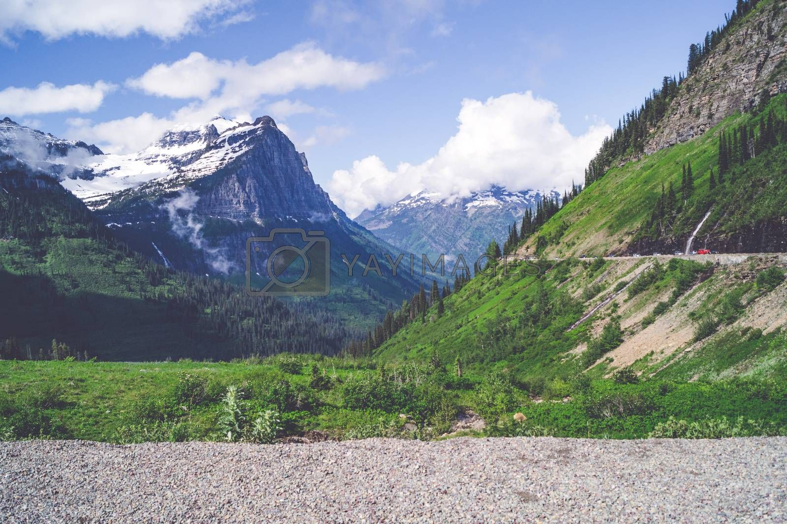 Mountain landscape with green grass and snow on the top