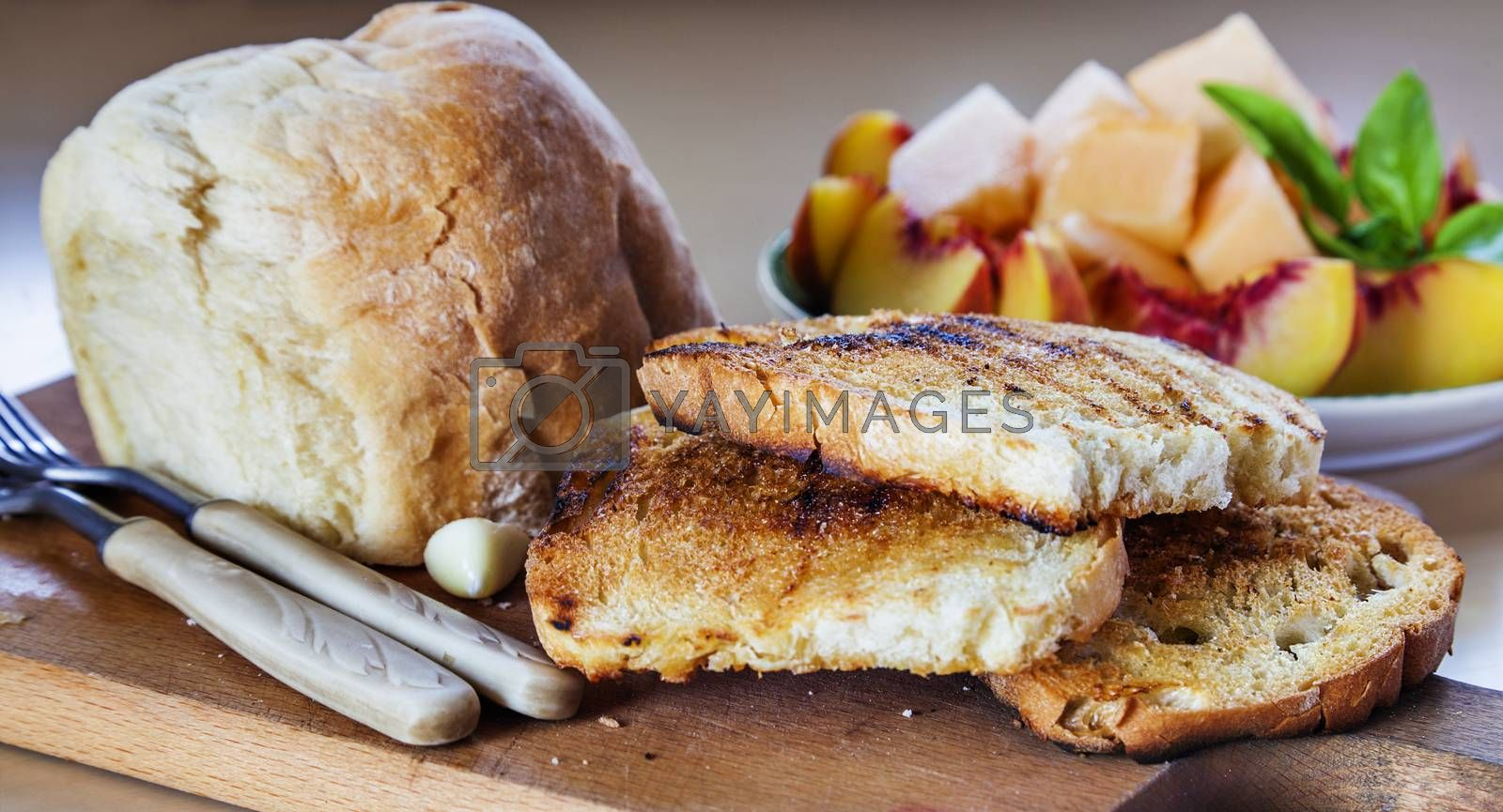 Three roasted slices of bread with garlic, fresh bread and a plate of sliced fruits behind.
