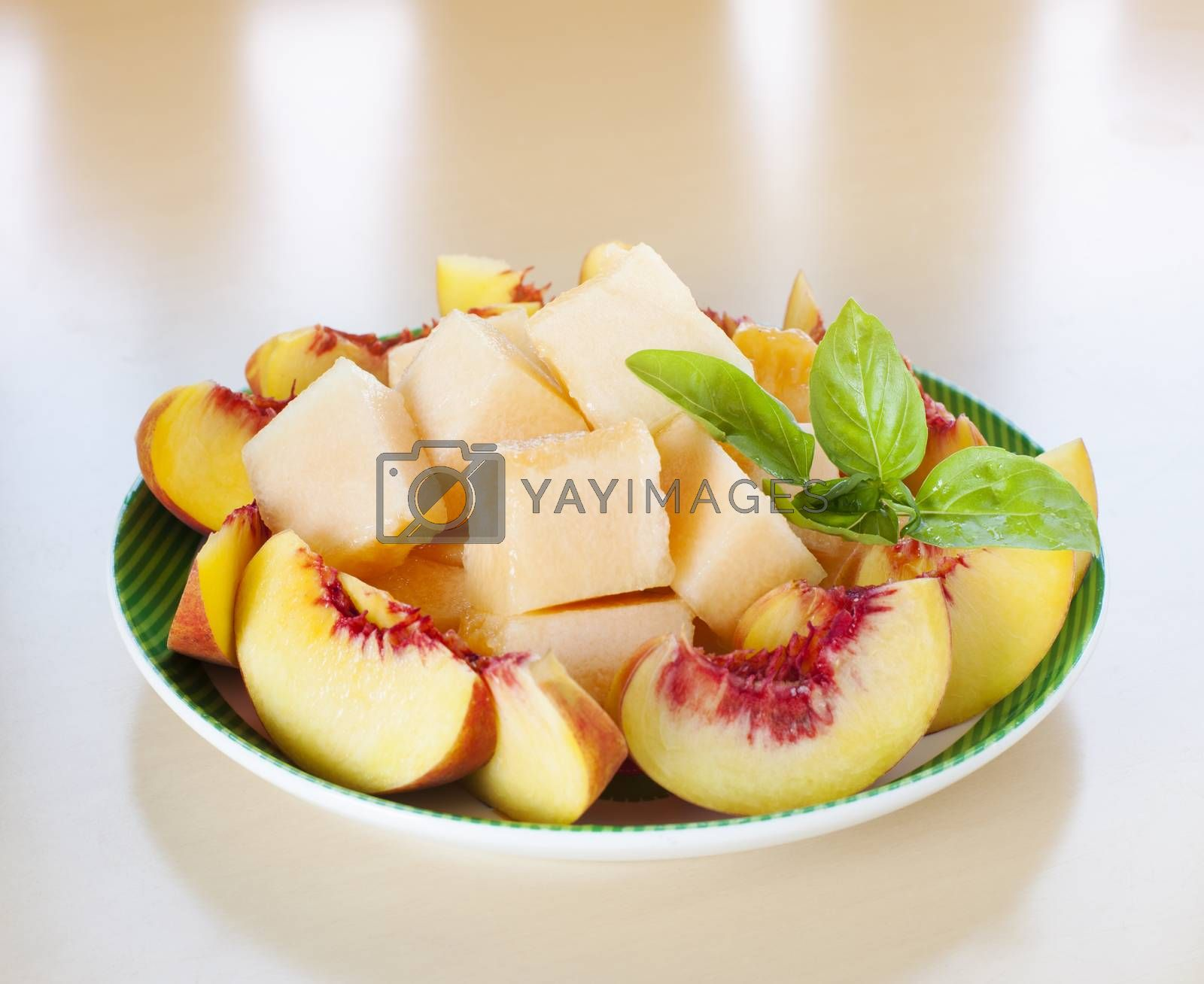 Plate with sliced fruits - peaches and melon with fresh basil.