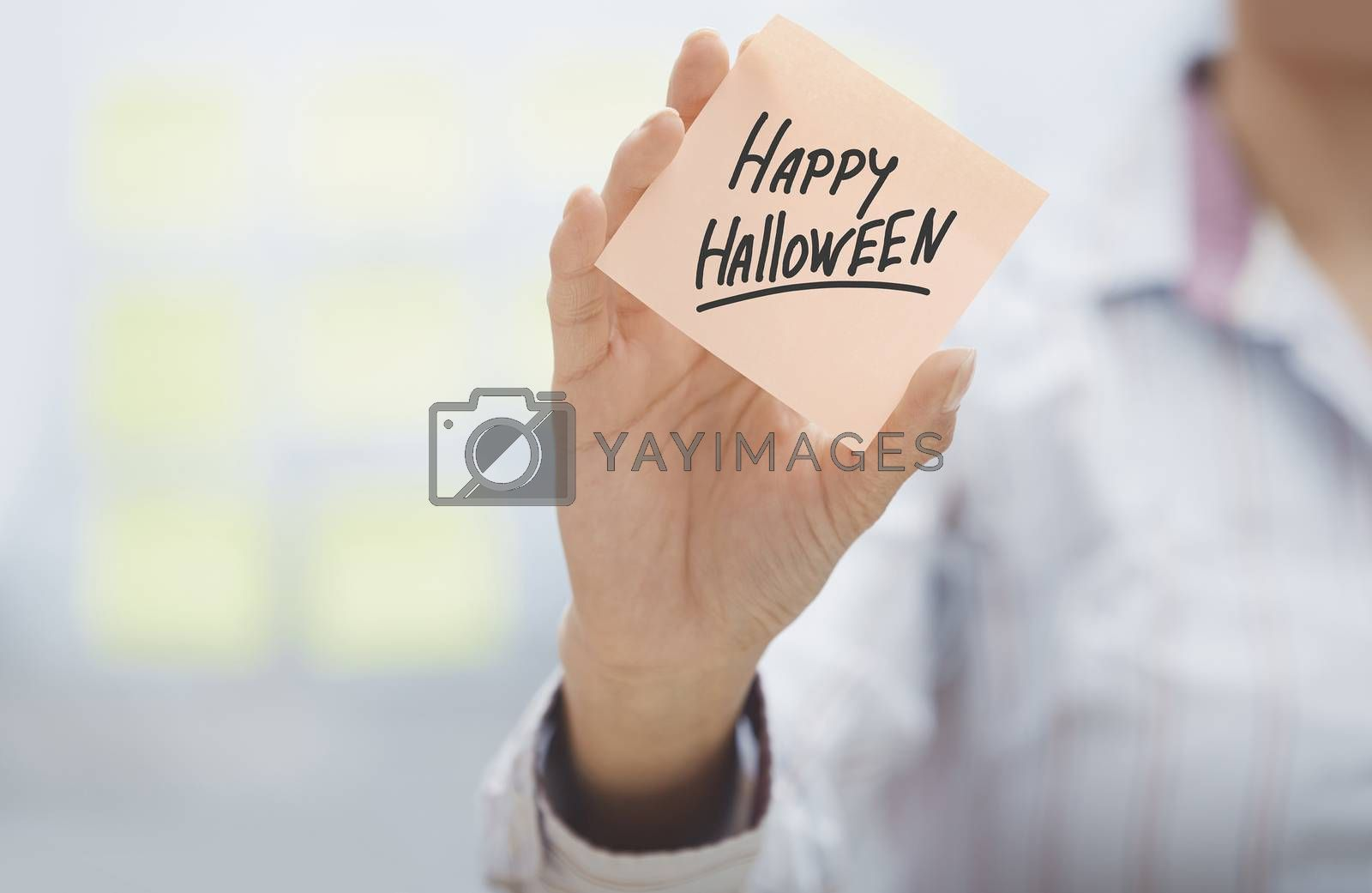 Woman holding sticky note with Happy Halloween text