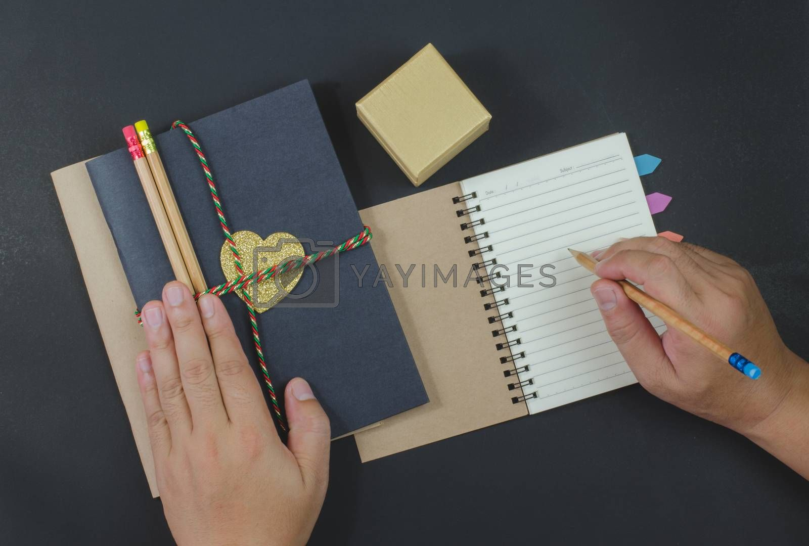 write paper notebook pencils on black background