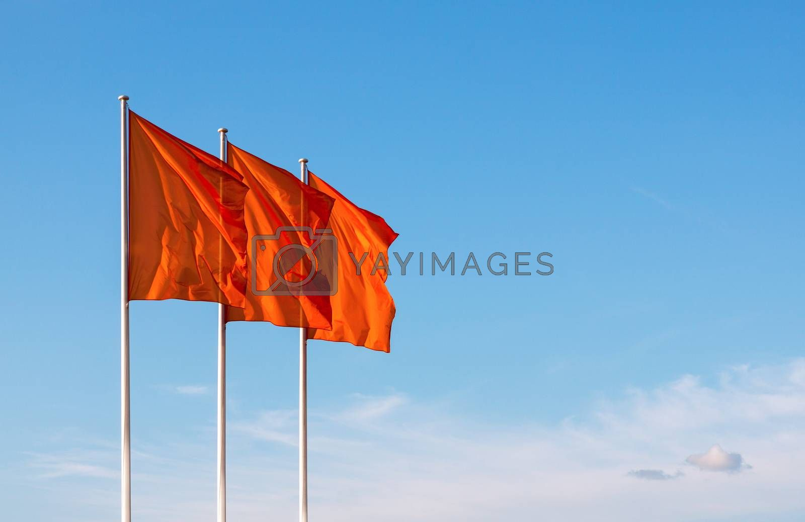 Three red blank flags waving in the wind against cloudy sky. Perfect mockup to add any logo, symbol or sign