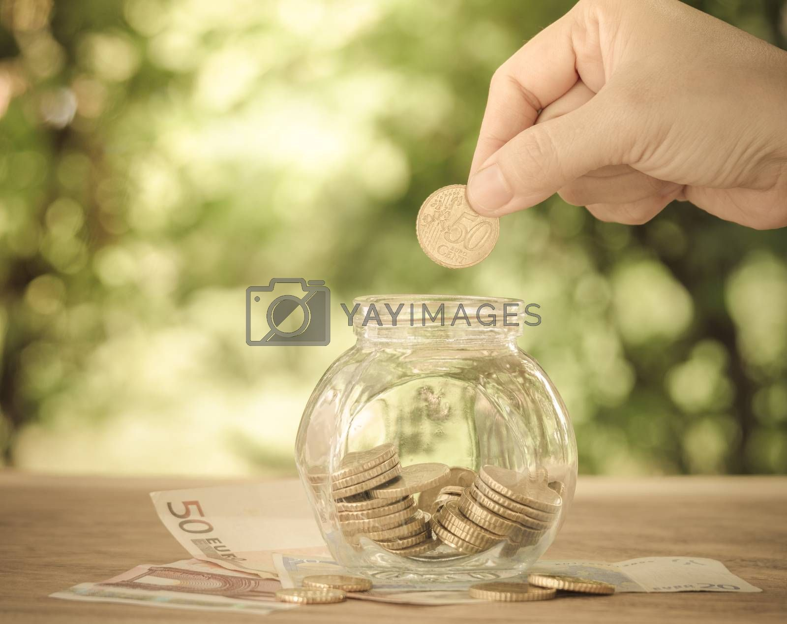 hand's women putting golden coin in money jar. account concept,business concept,finance concept. vintage style.