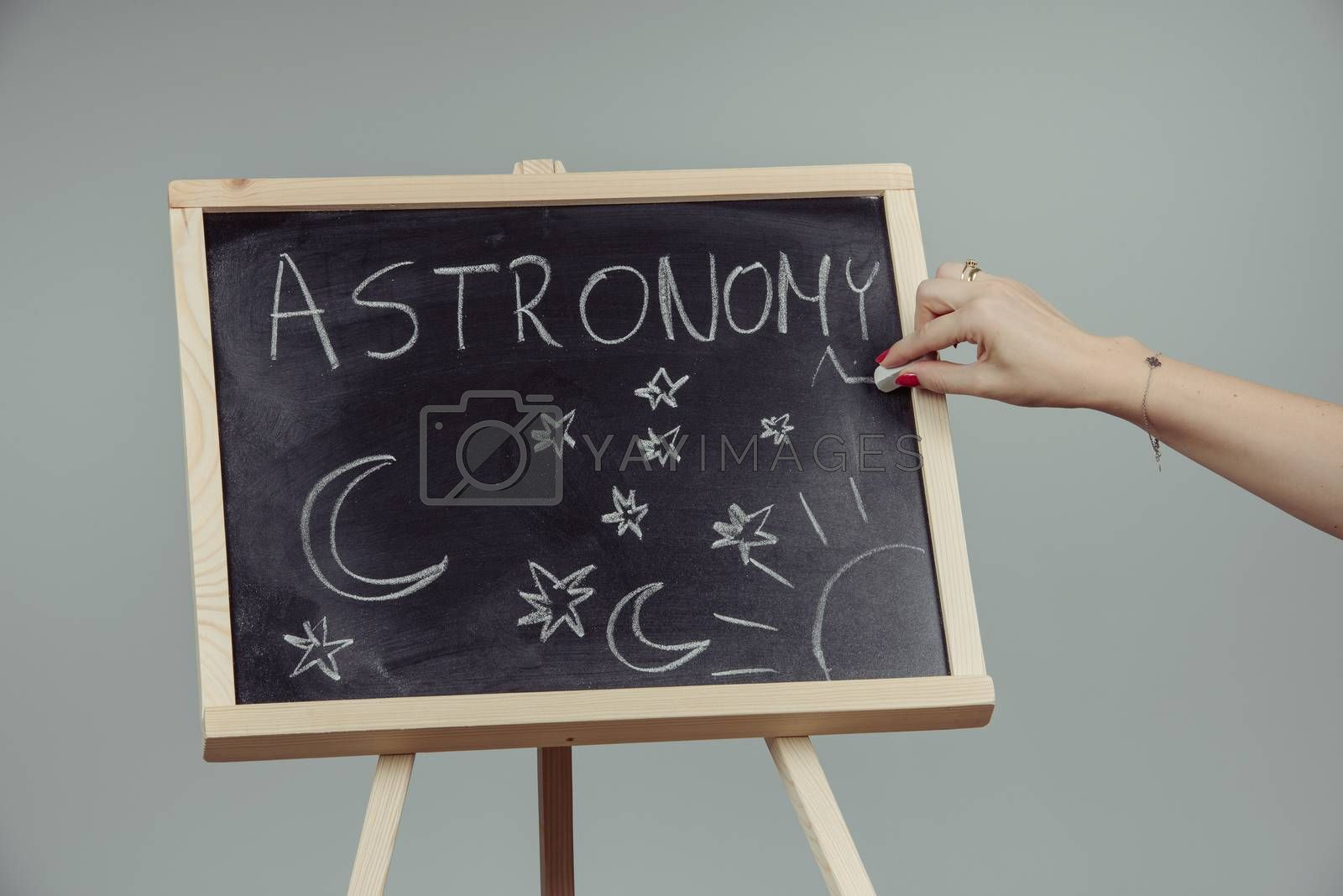 Woman draw on chalkboard astronomy subject. Gray background