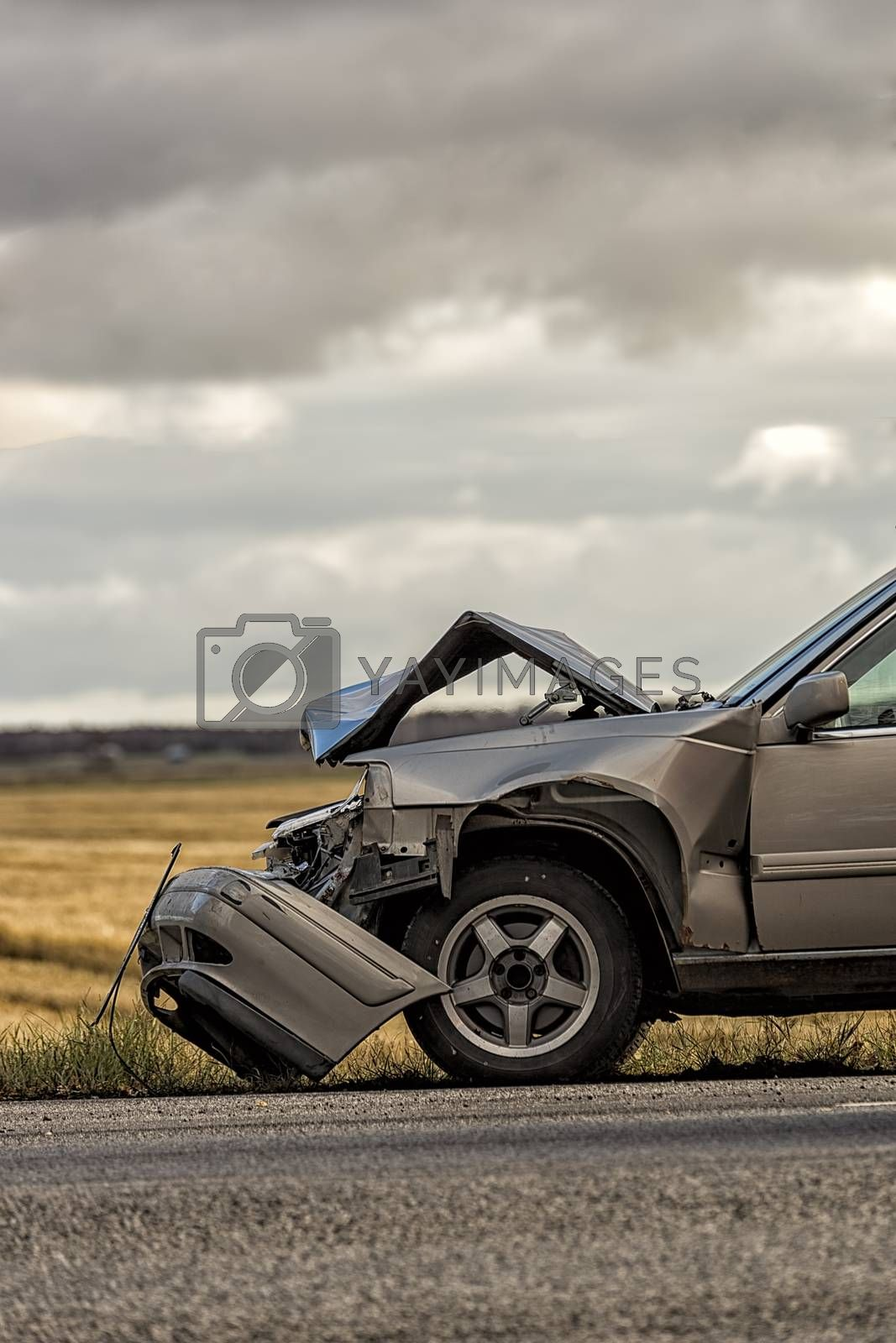 Car Crashed after Accident with a field and cloudy sky.