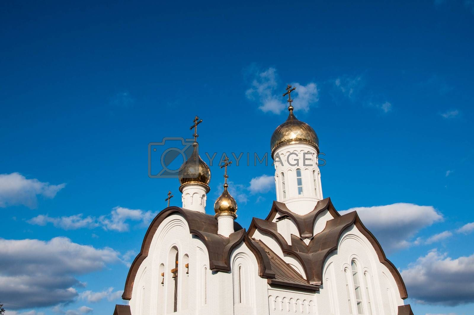 The dome of the Christian Church against the background of blue sky and white clouds.
