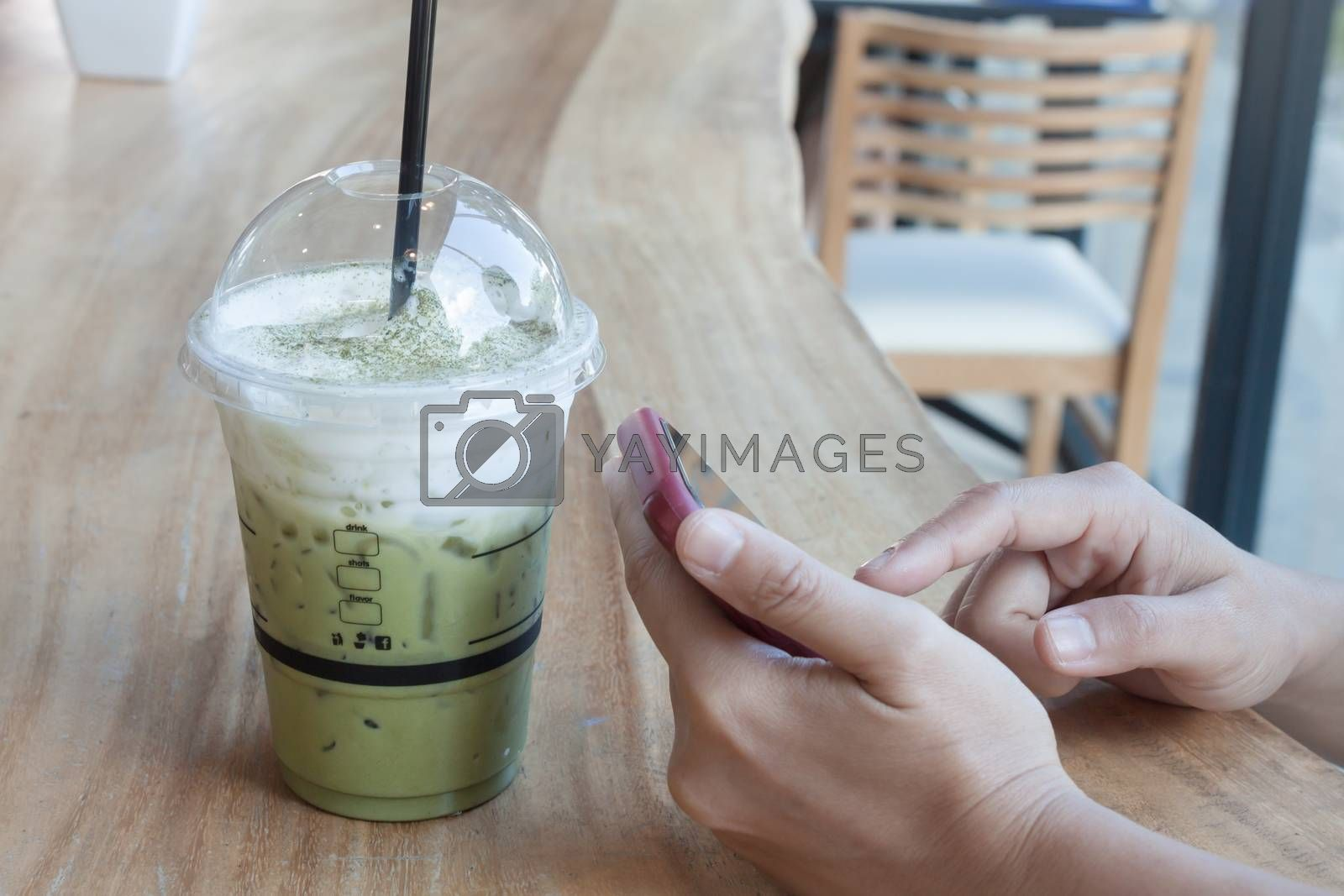 Woman hand holding phone with background of iced green tea, stock photo