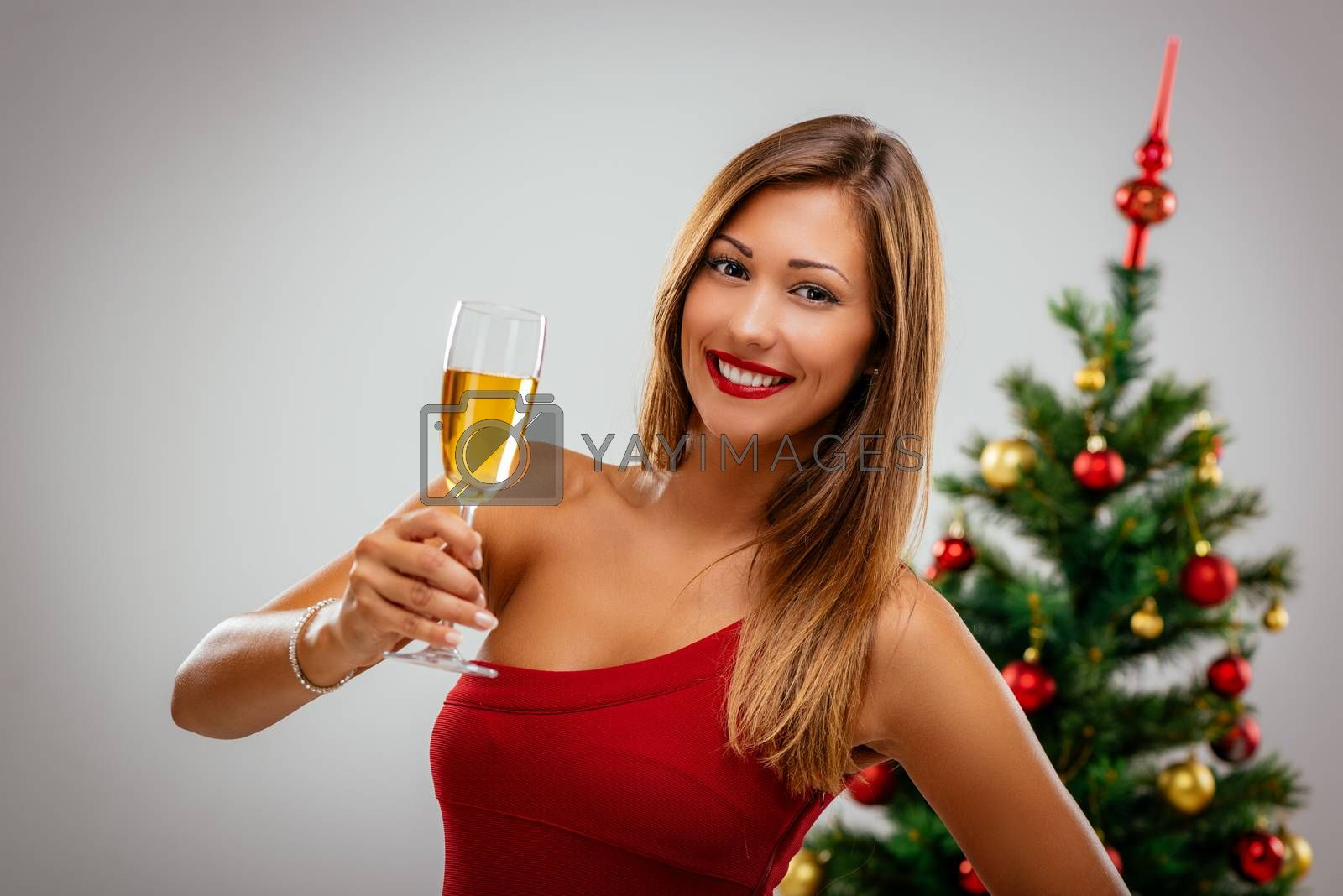 Beautiful young smiling woman in red dress toasting with champagne. Looking at camera.