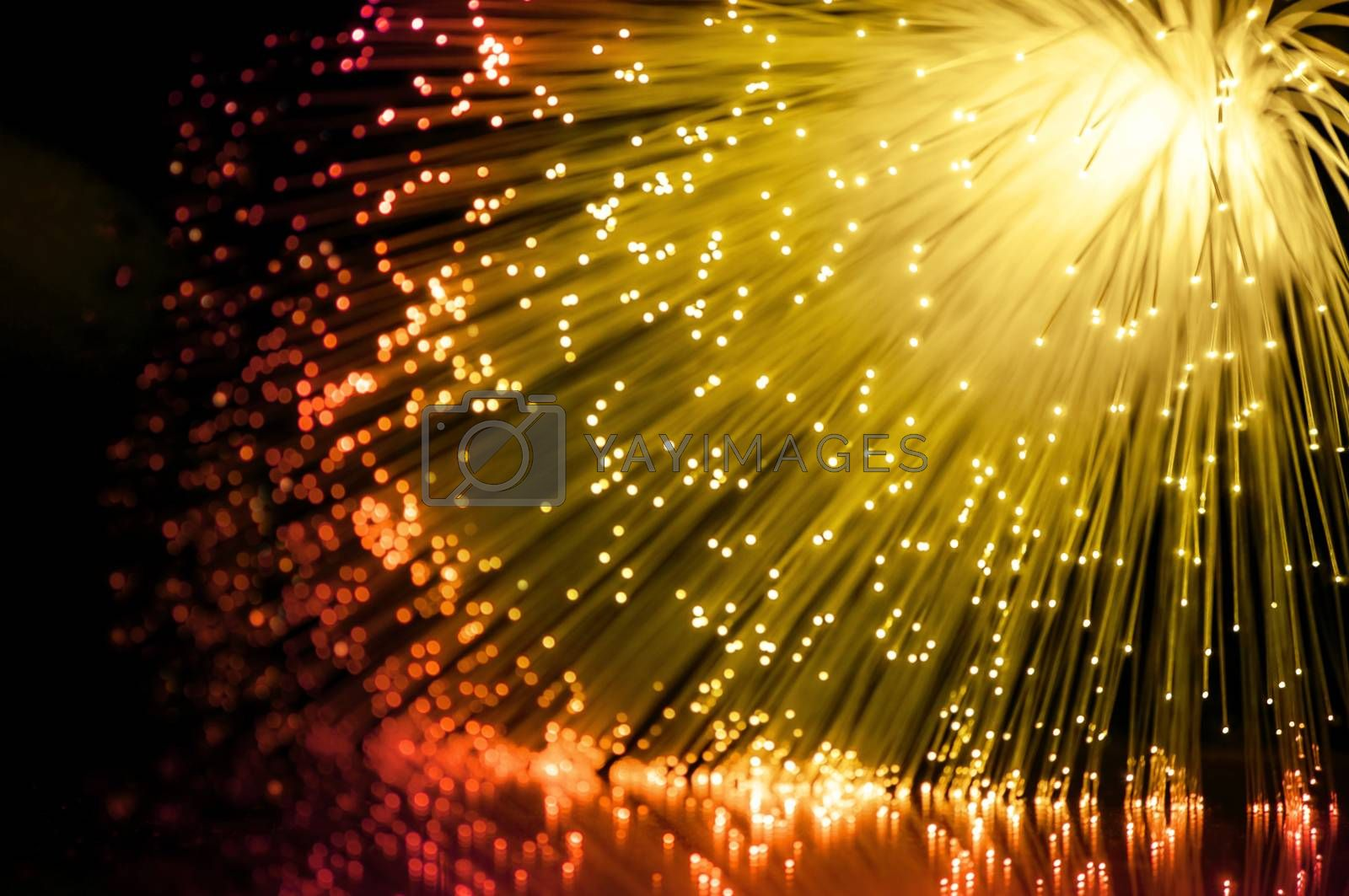Abstract golden and red fiber optic scene arranged over black.