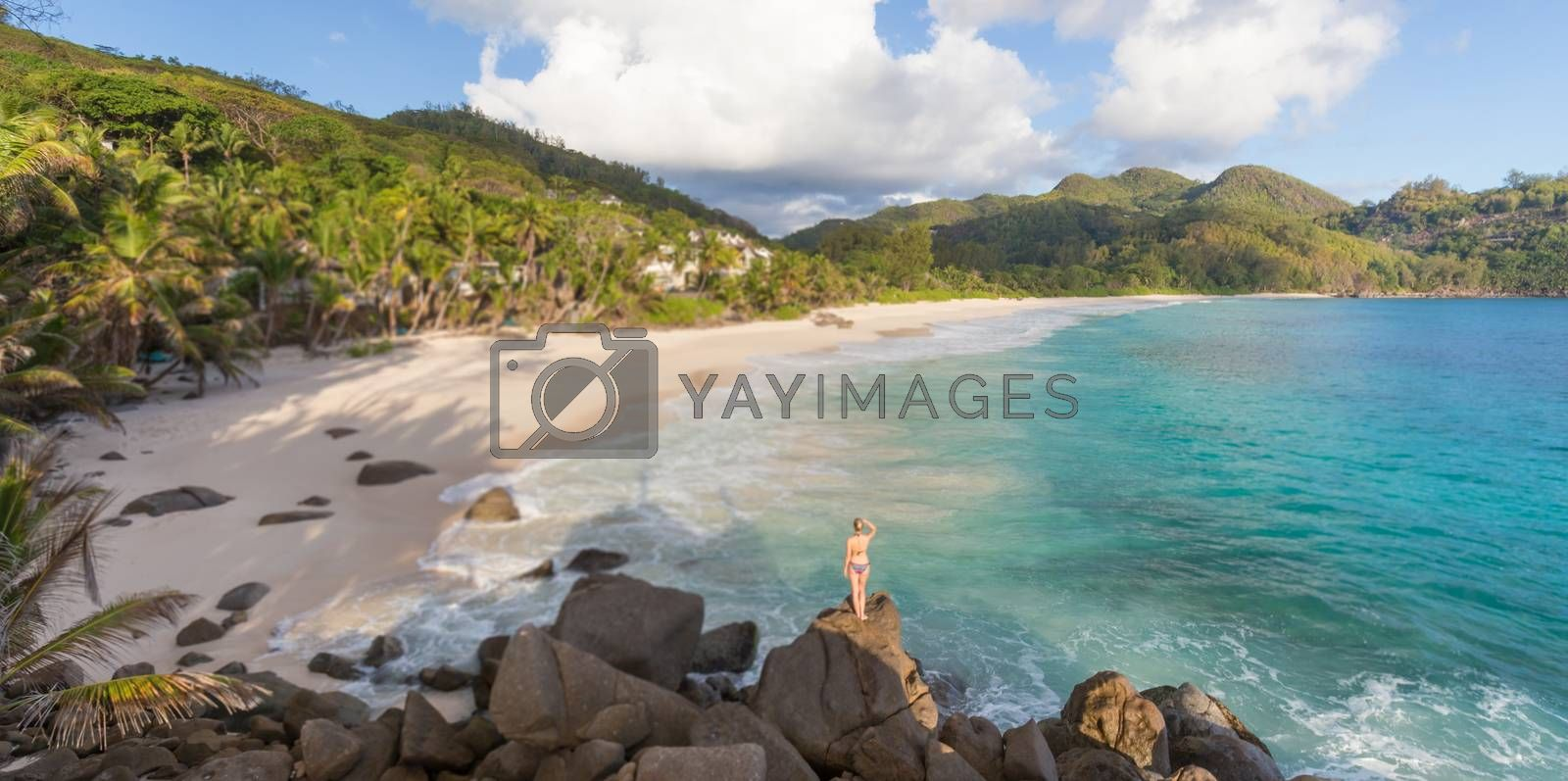 Woman in bikini enjoying beautiful view of Ance Intendance paradice beach from perfect round rocks on Mahe Island, Seychelles. Summer vacations on picture perfect tropical beach concept.