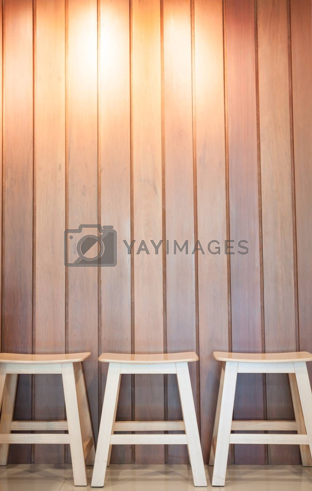 Three wooden chairs on wall background, stock photo
