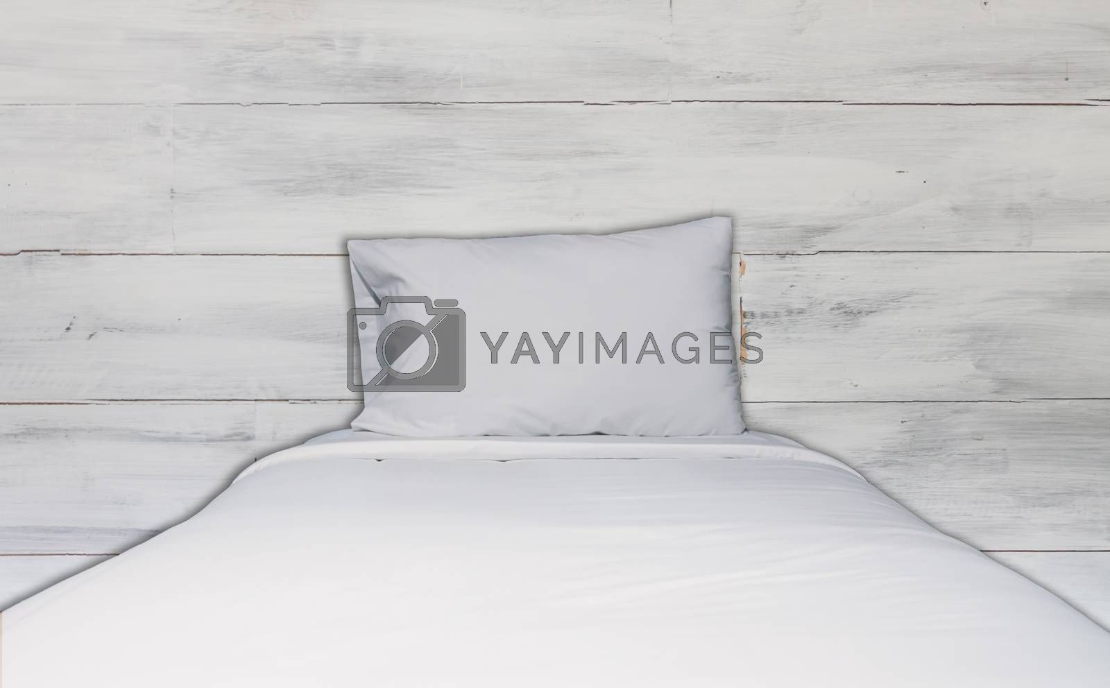 Close up white bedding sheet and pillow with white wooden wall texture background