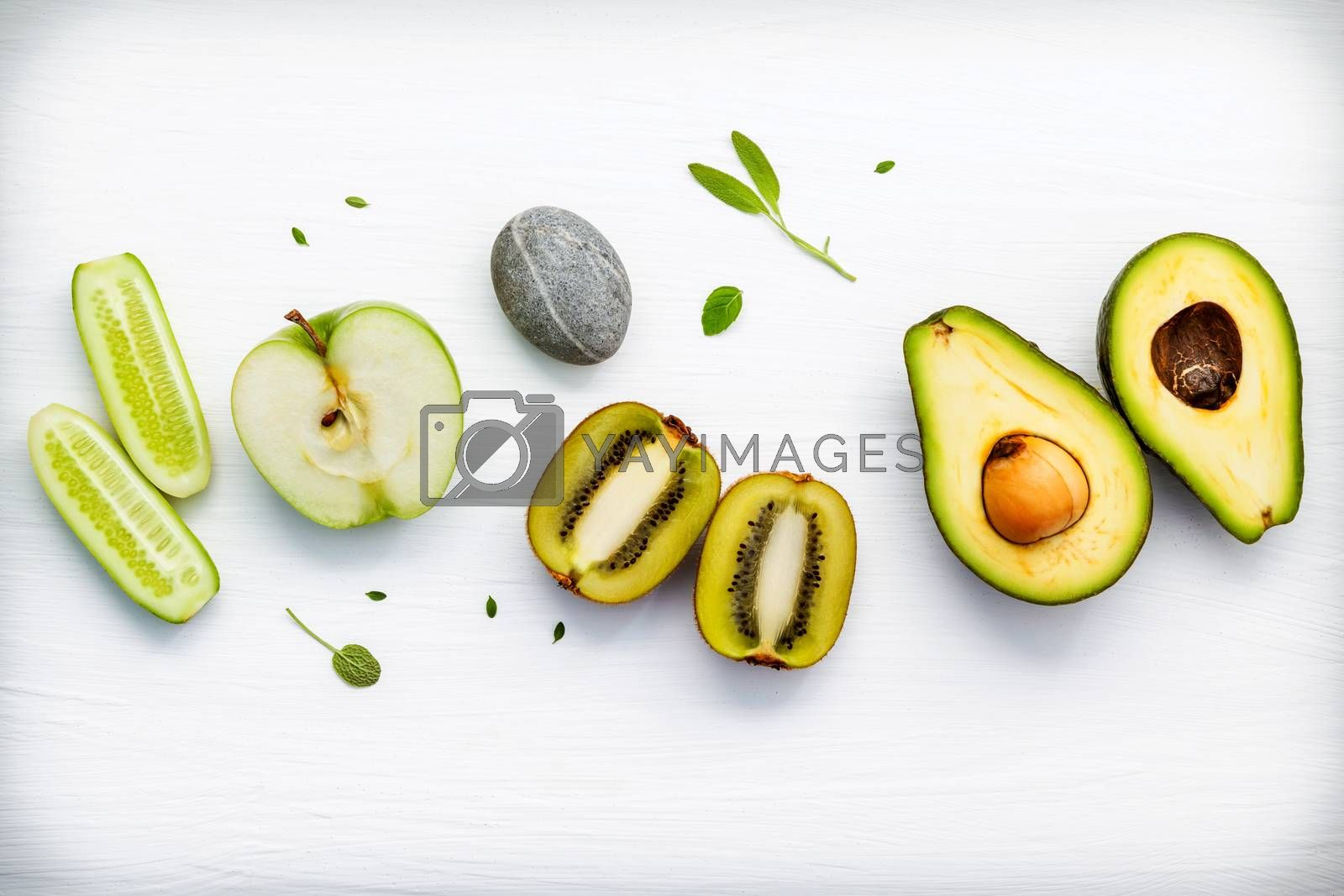 Homemade skin care and body scrubs with green natural ingredients cucumber , avocado ,green apple,kiwi, and spa stone setup on white wooden background with flat lay. Zen spa and oriental spa theme.