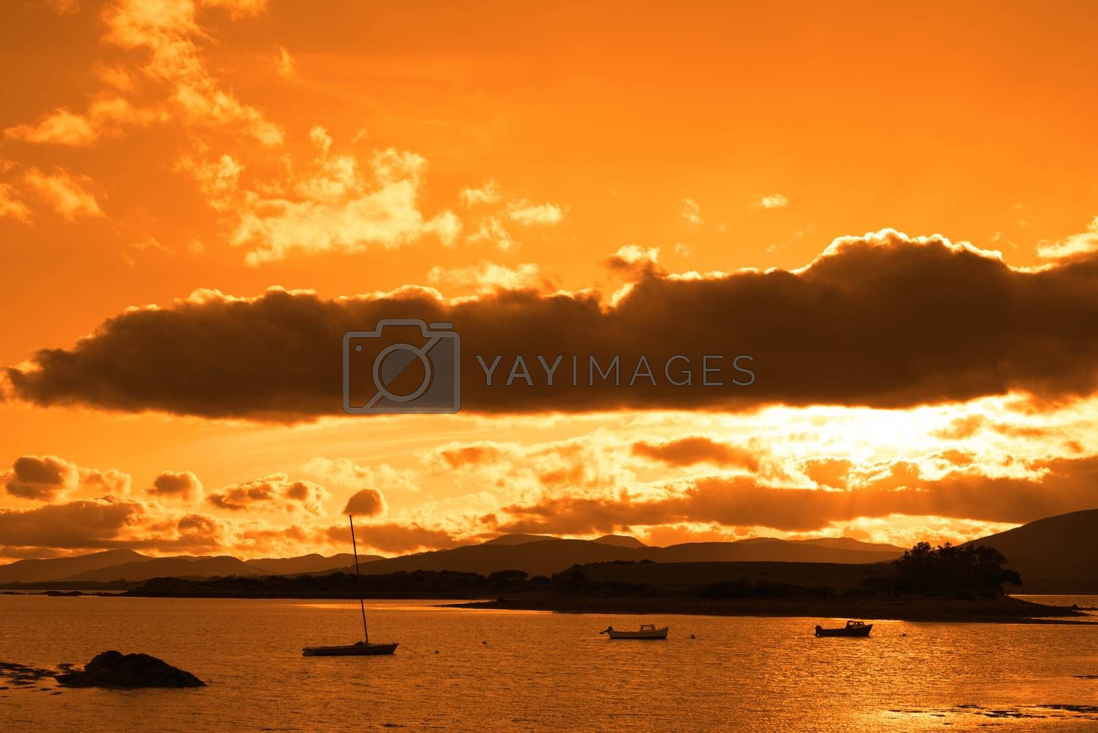 boats in a quiet bay with island near kenmare on the wild atlantic way ireland with an orange sunset