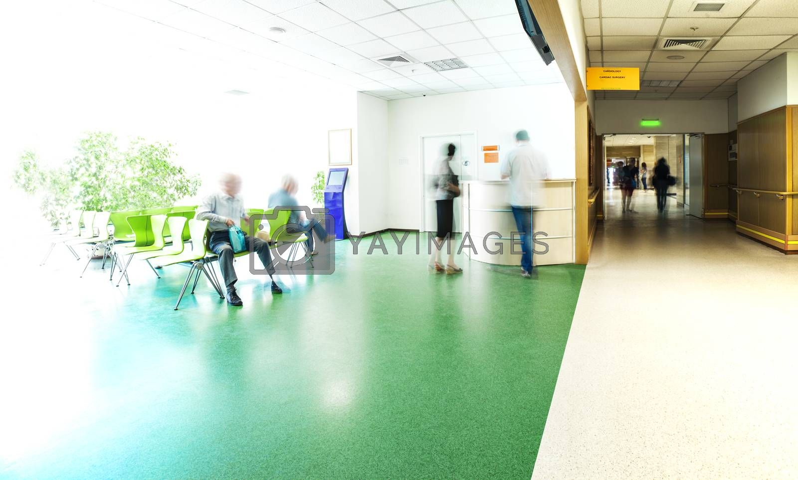 View of the registration desk, waiting area and a corridor in modern hospital with blurred figures of patients with a copy space.