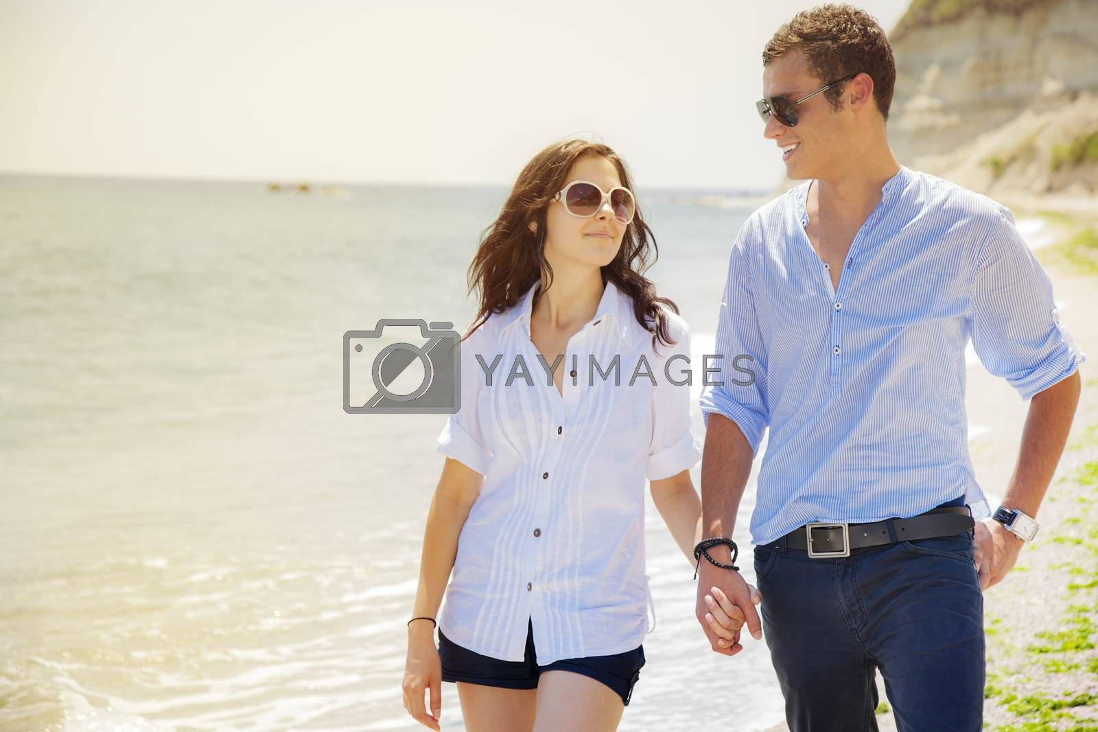 Couple in love walking by the sea hand in hand looking at each other.