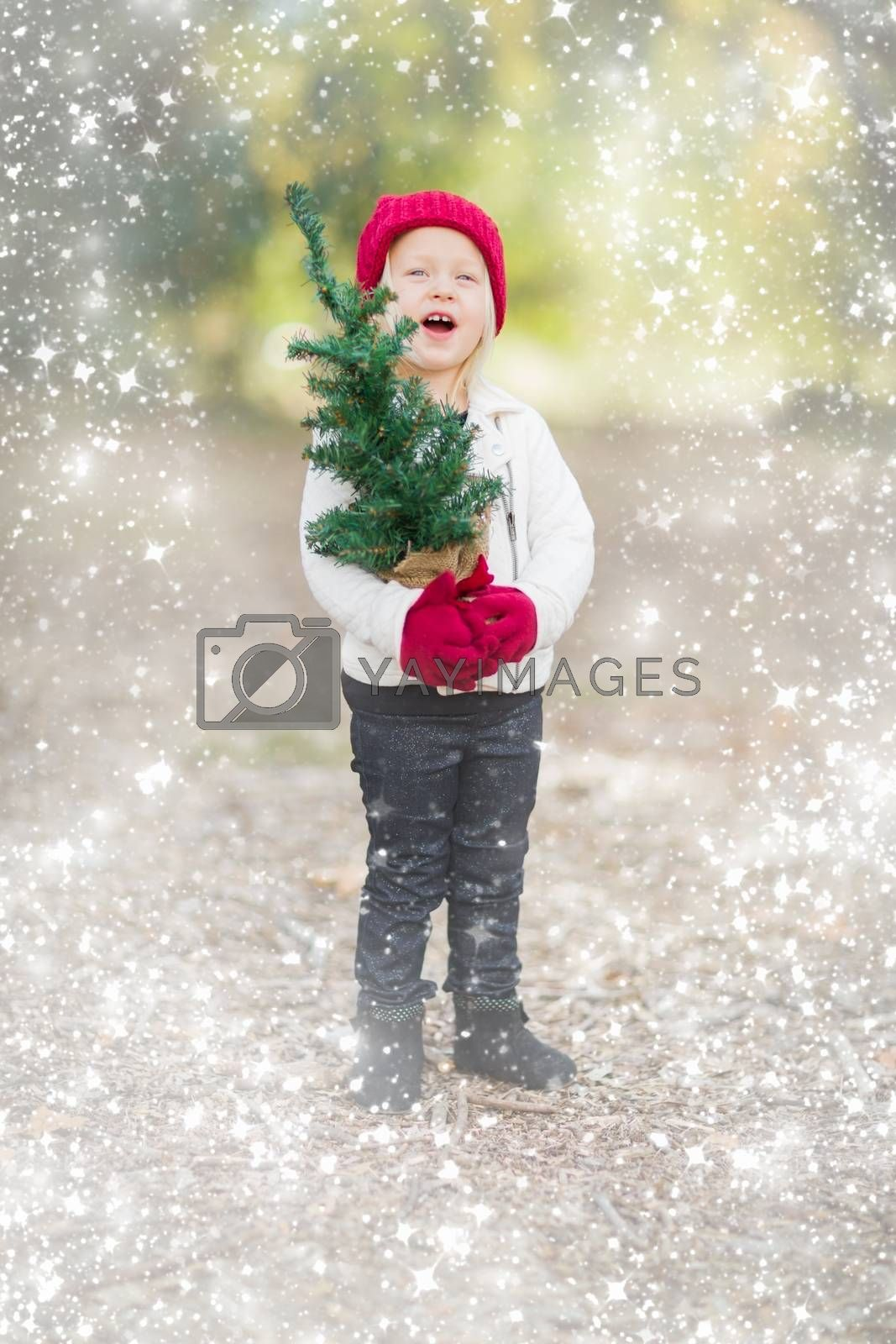 Baby Girl In Red Mittens and Cap Holding Small Christmas Tree Outdoors with Snow Effect.
