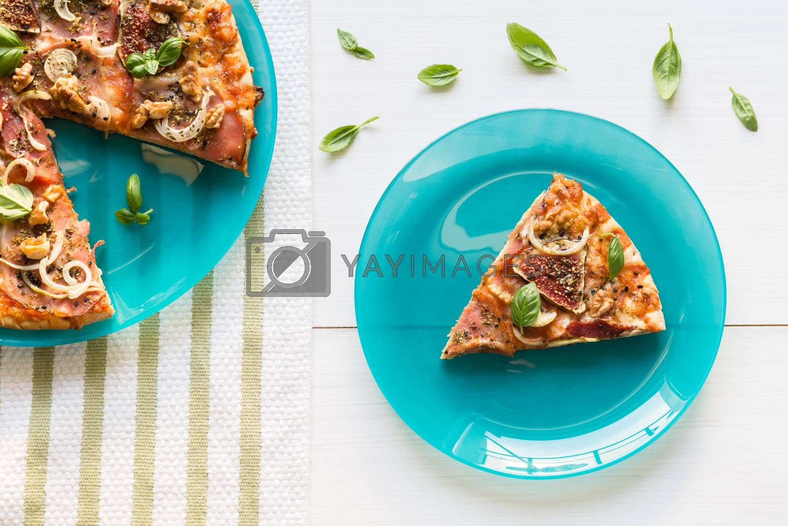Top view of pizza with figs, prosciutto, onion and fresh basil on a turquoise plate and white table