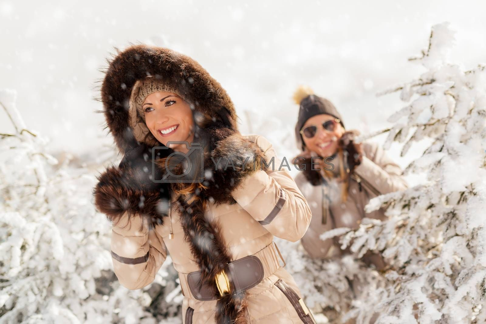 Two beautiful happy female friends taking a walk while its snowing.