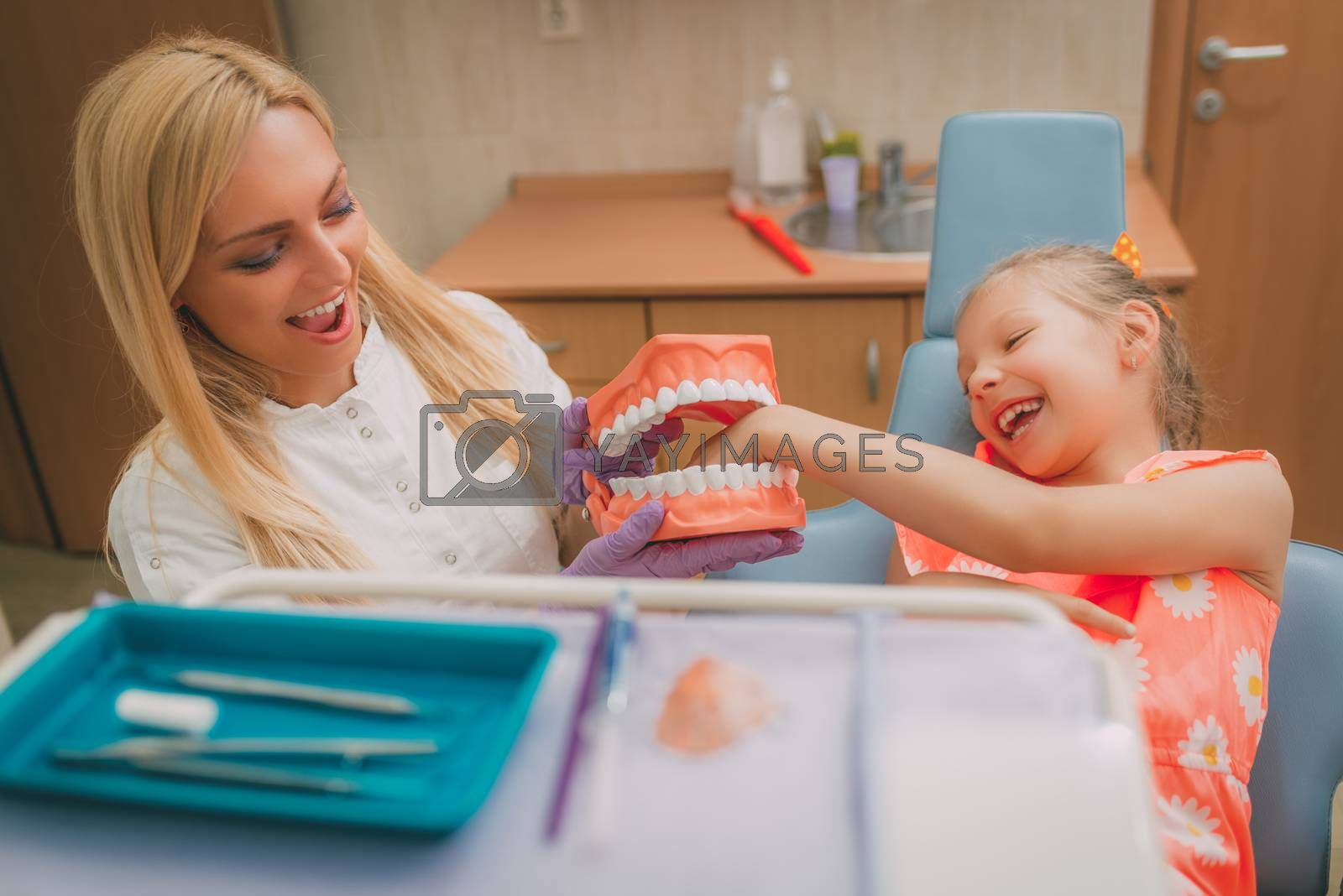 Beautiful little girl at visit in the dentist office. She and female dentist having fun with big teeth.
