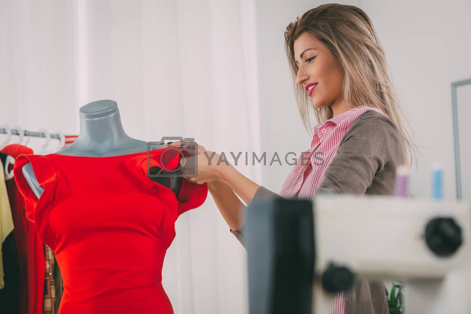 Young woman, fashion designer, creates a dress on mannequin. In addition to the mannequin on the table is sewing machine. Selective focus. Focus on a background.
