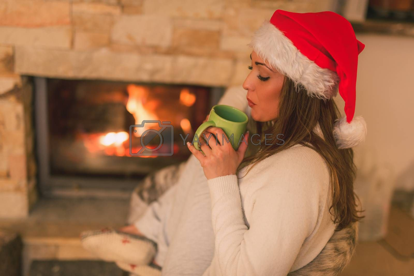 Beautiful young smiling woman with santa hat enjoying a cup of tea by the fireplace.