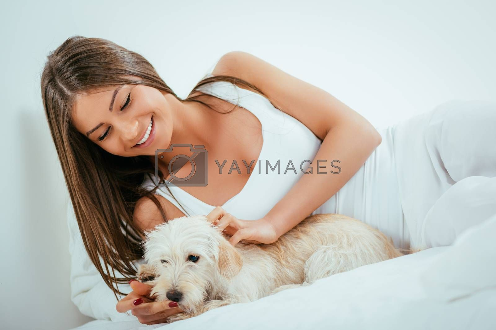 Beautiful young woman and her dog relaxing in bed in the morning.