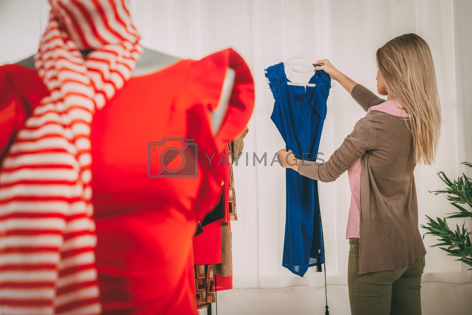 Fashion designer at the office looking dress. In the foreground you can see a dress on mannequin. Selective focus. Focus on background.