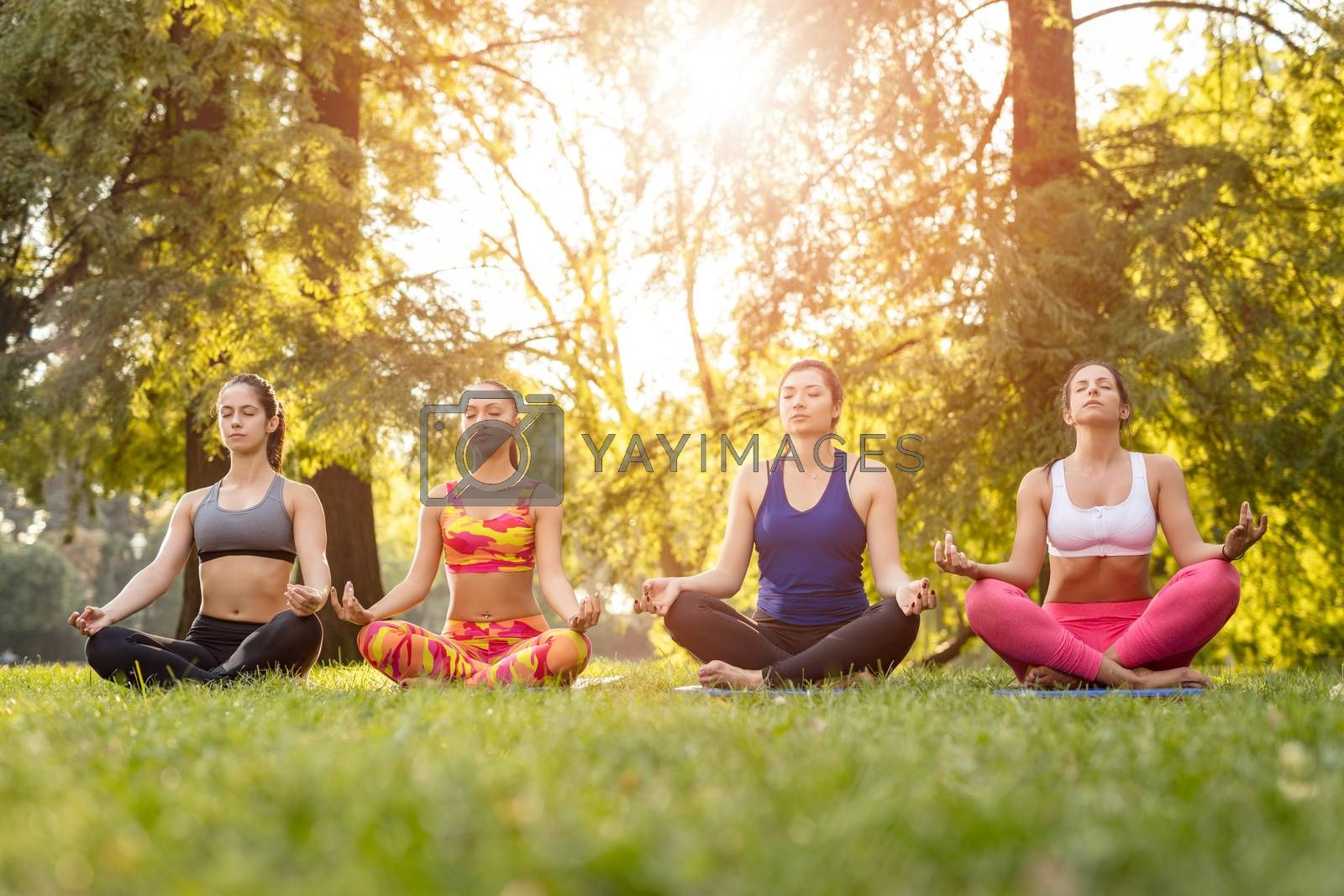 Four beautiful female friends meditating in the park.