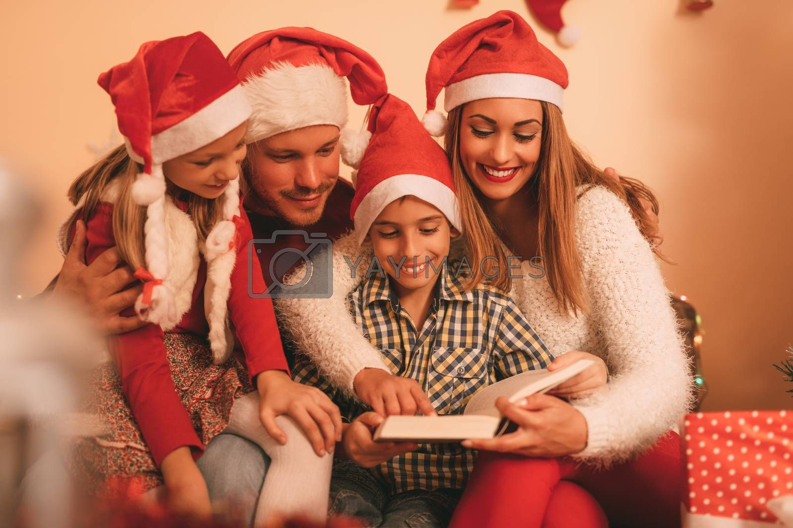 Beautiful smiling family of four with santa hat reading book at the home.