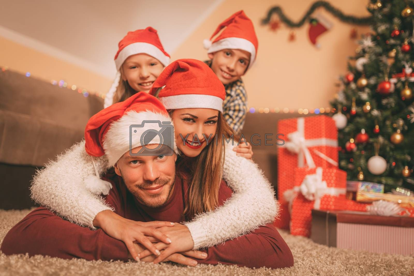 Beautiful smiling family with santa hat having fun next to a Christmas tree and many gift and looking at camera. They are at the home. Selective focus.