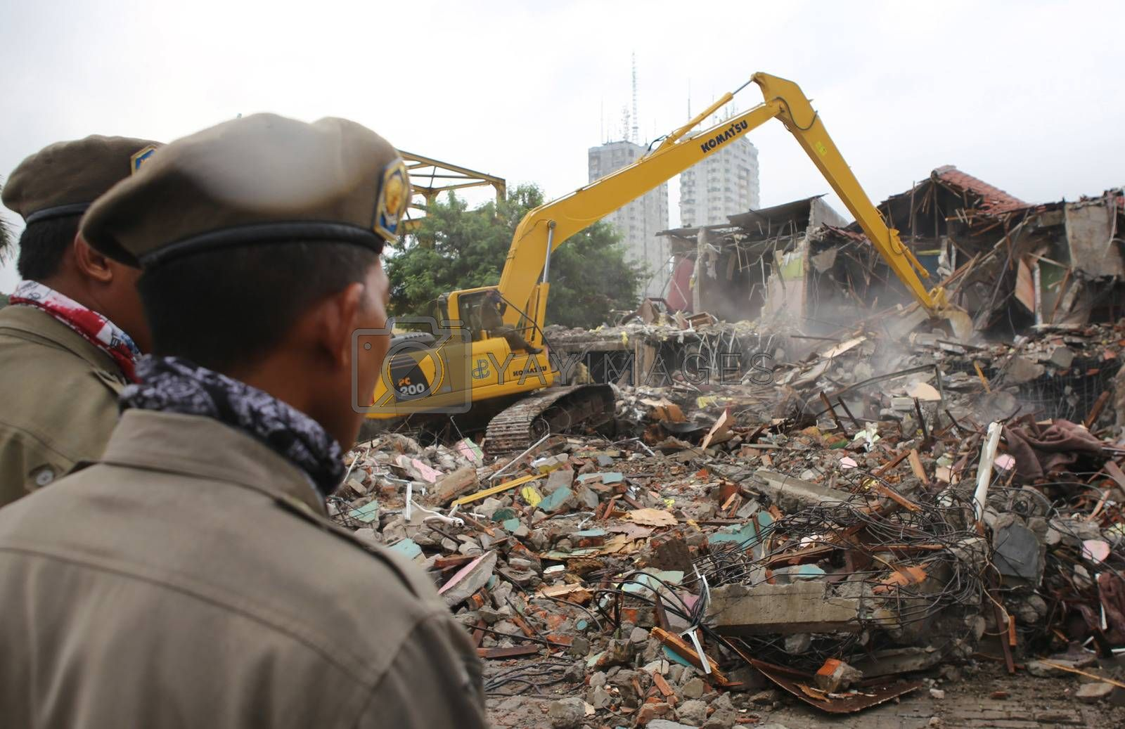 INDONESIA, Jakarta: Two policemen watches the demolition of houses of the Kalijodo red light district, in the Penjaringan subdistrict on the border of North and West Jakarta, on February 29, 2016. The neighborhood is home to about 3,000 people, including legal businesses and families. Hundreds face eviction for living among illegal brothels.