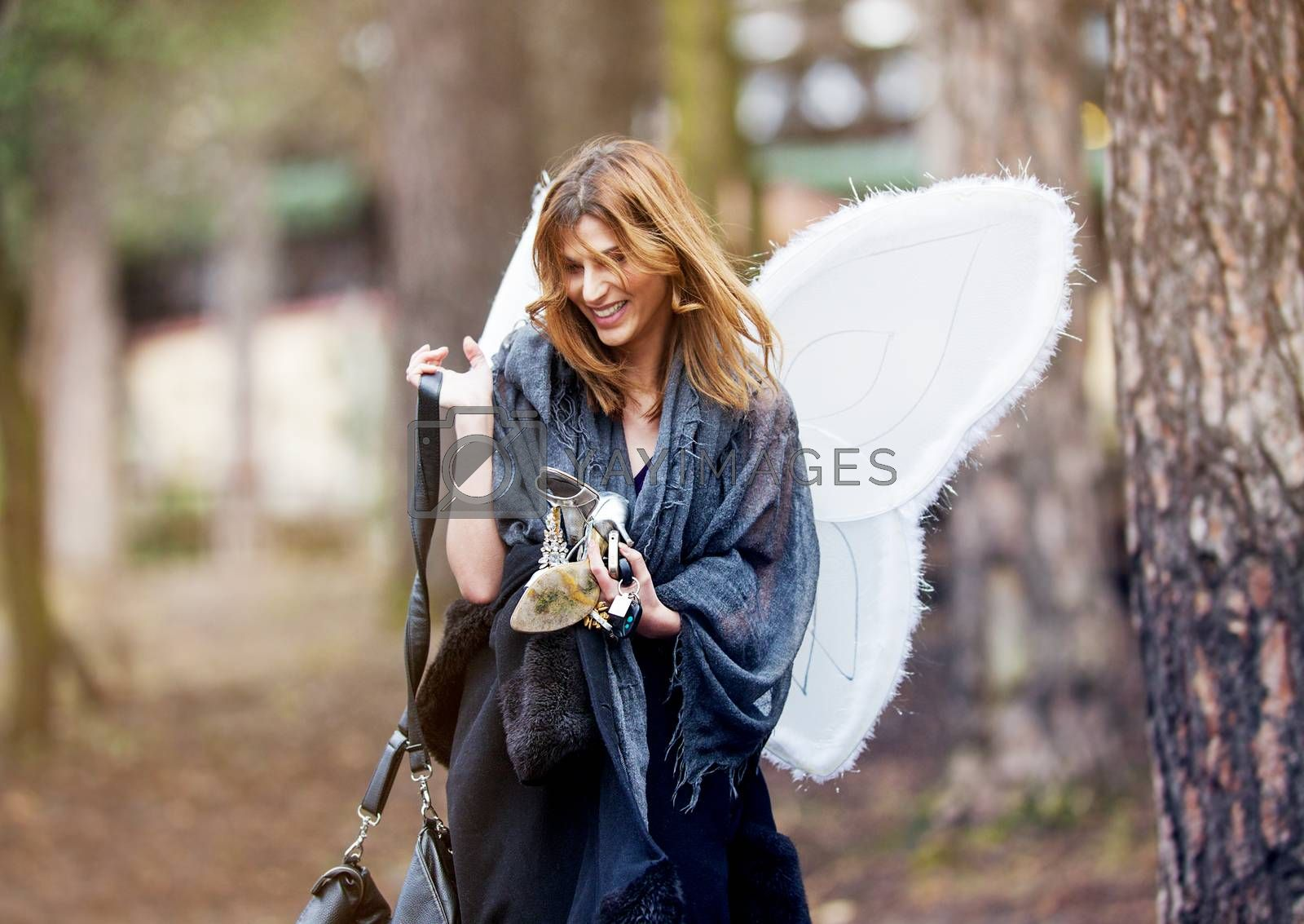 A beautiful happy smiling girl walking through the park with party angel wings and high heels in her hands.
