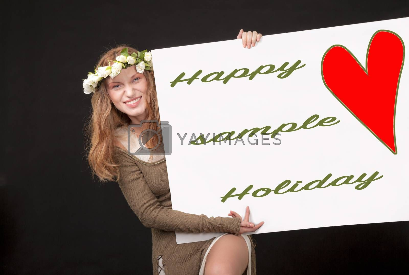 A playful beautiful woman with white roses wreath in her long hair is holding and showing a sign with red heart, sample text and a clipping path.